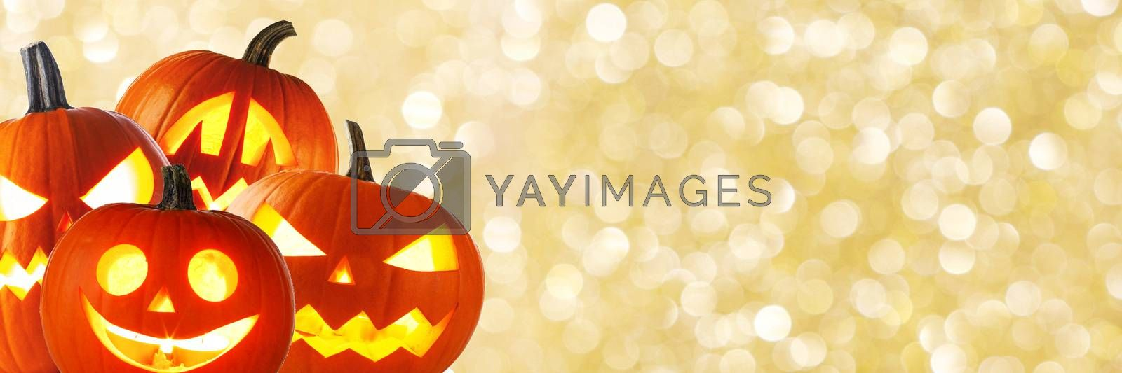 A collection of Jack O Lantern Halloween pumpkins with various different design on golden bokeh background with copy space