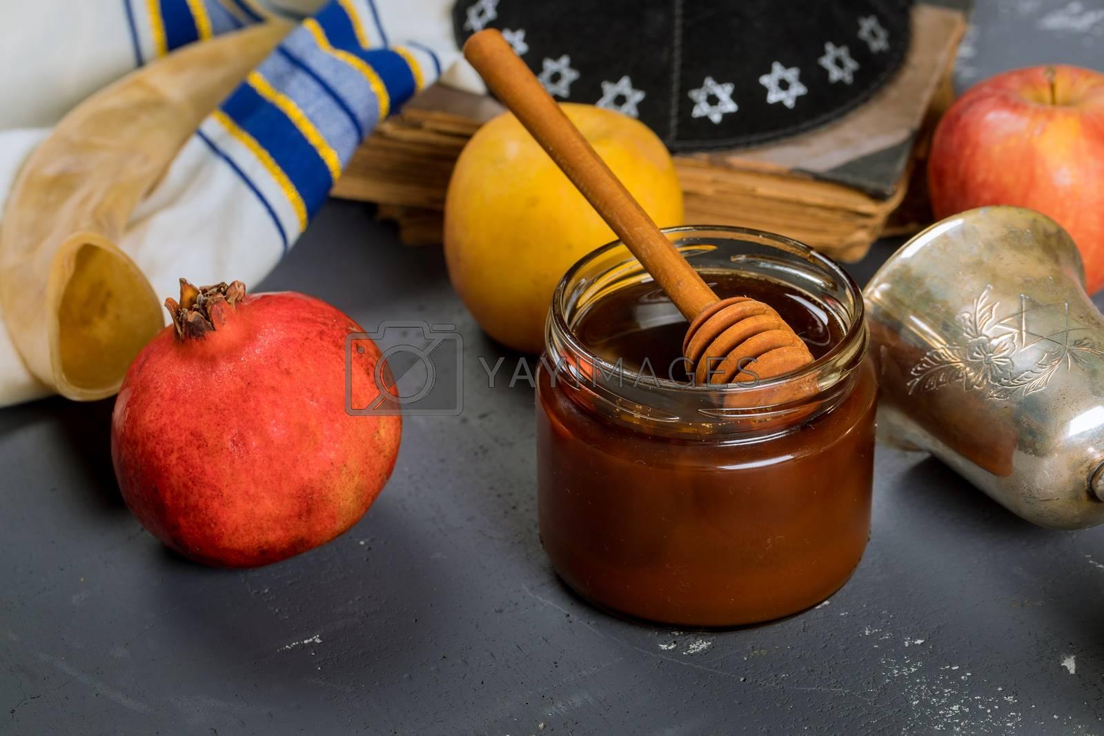 Honey on the pomegranate and apples. Jewishs new year Rosh Ha Shana kippah yamolka and shofar Orthodox Jewish prays at the praying book