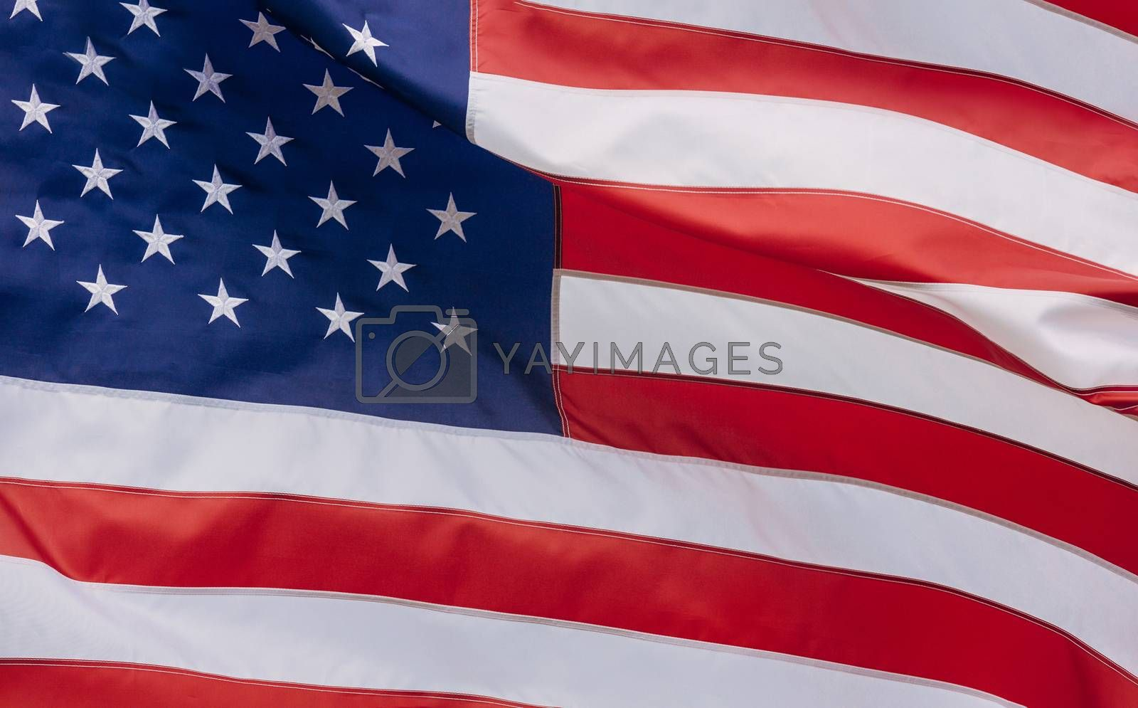 Royalty free image of Flag of the USA with sunflare by ungvar