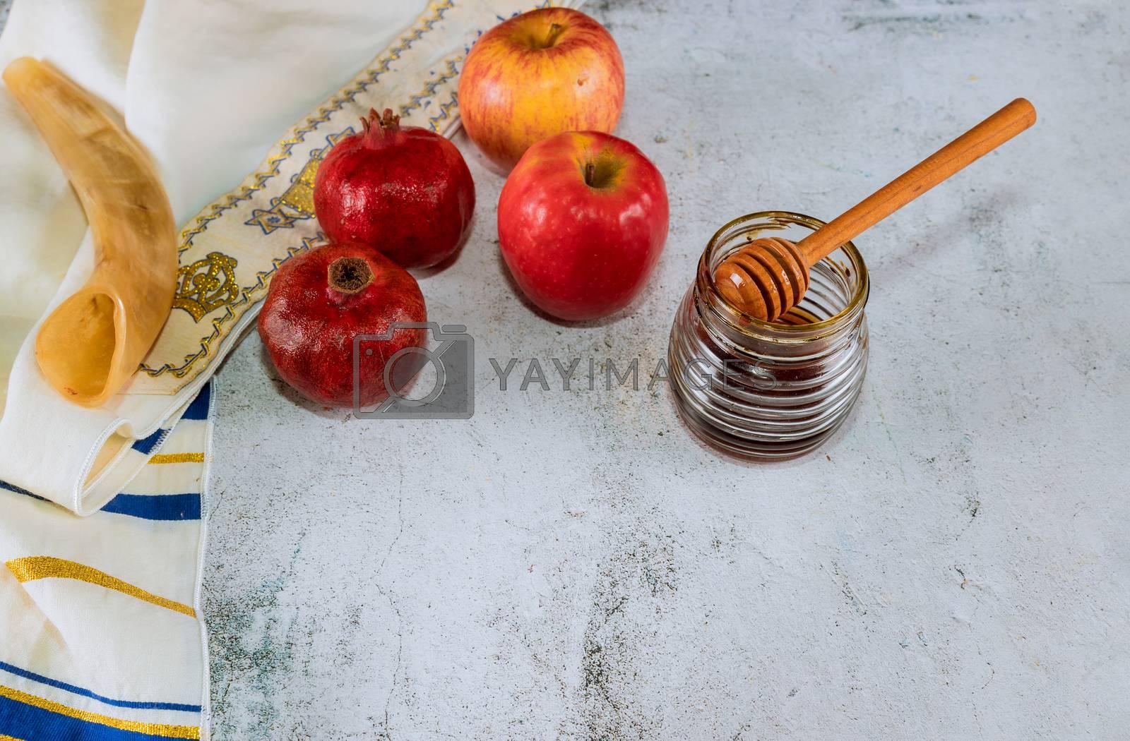 Honey on the pomegranate and apples. Jewish new year Rosh Ha Shana kippah yamolka and shofar Orthodox Jewish prays