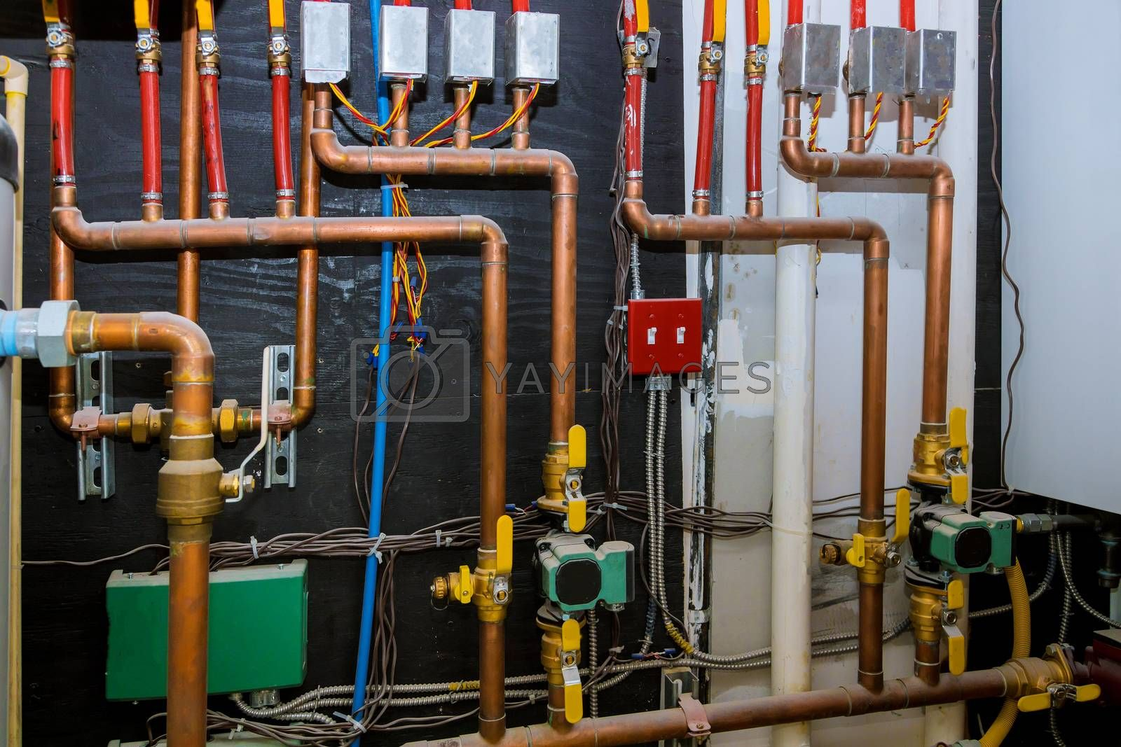 Heating system's copper pipes with ball valves on pipes collector of underfloor heating system pump and pipes