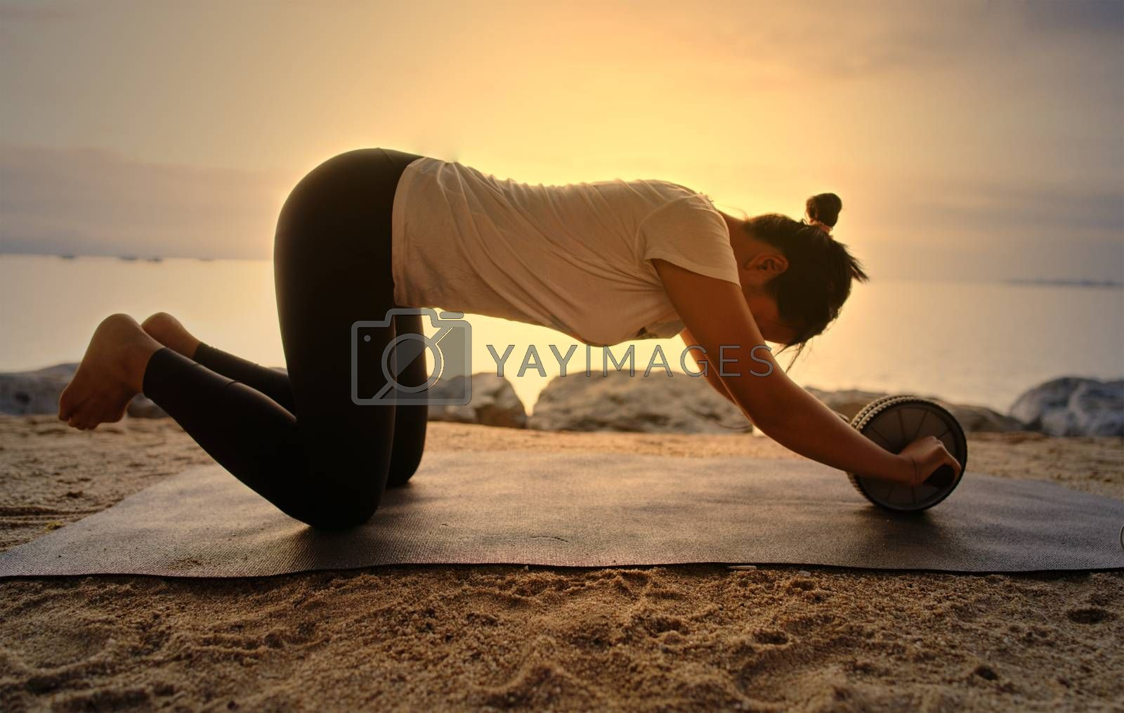 A young woman in sportswear stretches out with equipment by the shore at the setting sun of her vacation.