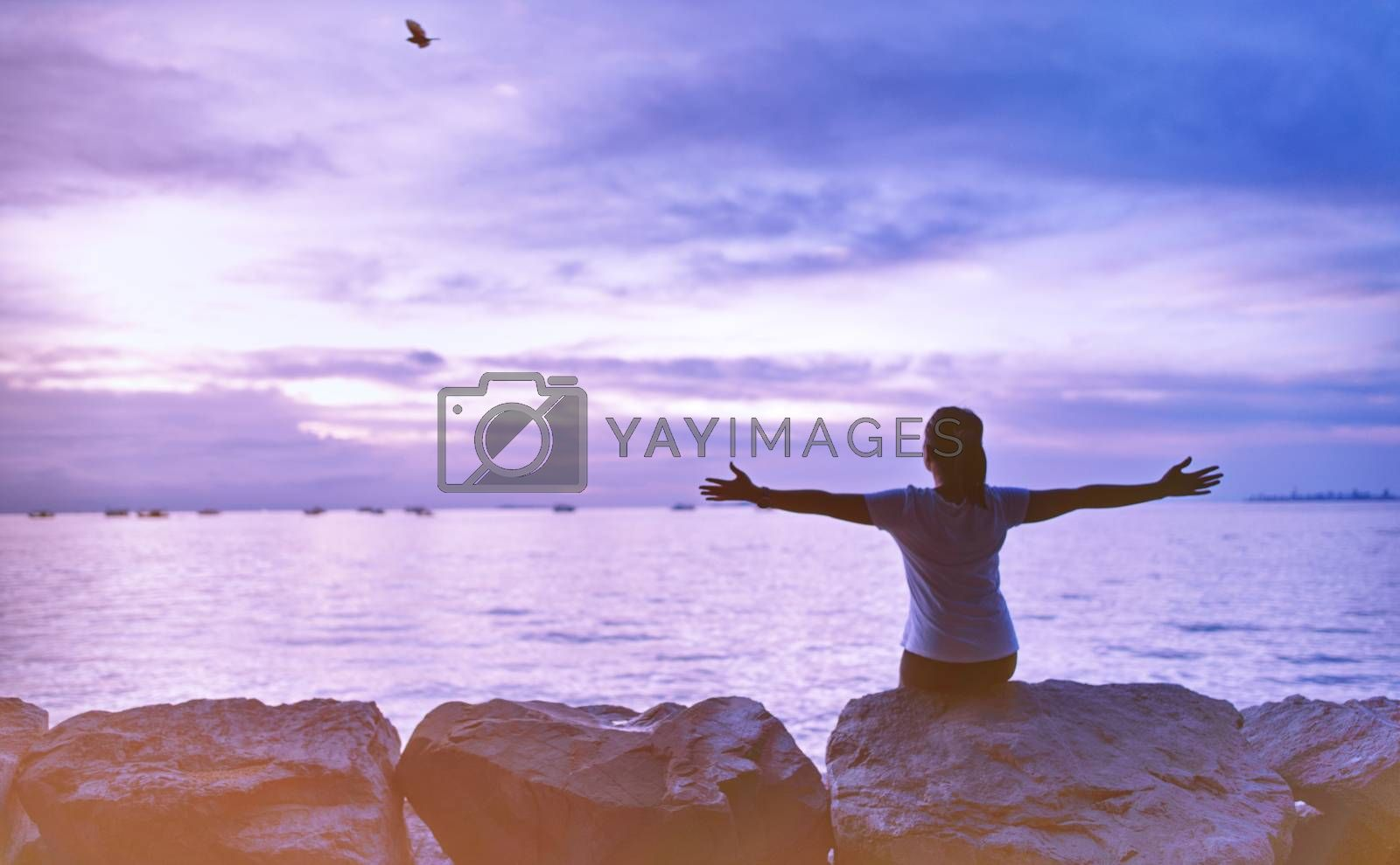 The silhouette of a woman sitting by the sea in the clear sky day of the vacation