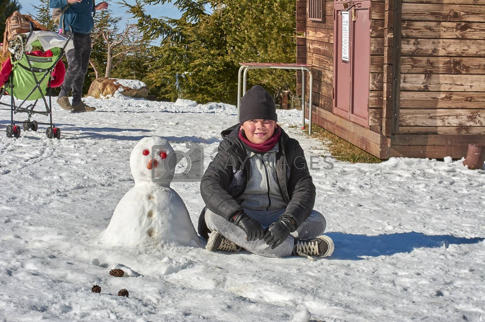 Family, boy, smiling, posing with snowman, playing and having fun in snow, ski resort, sierra nevada, granada, andalusia, spain