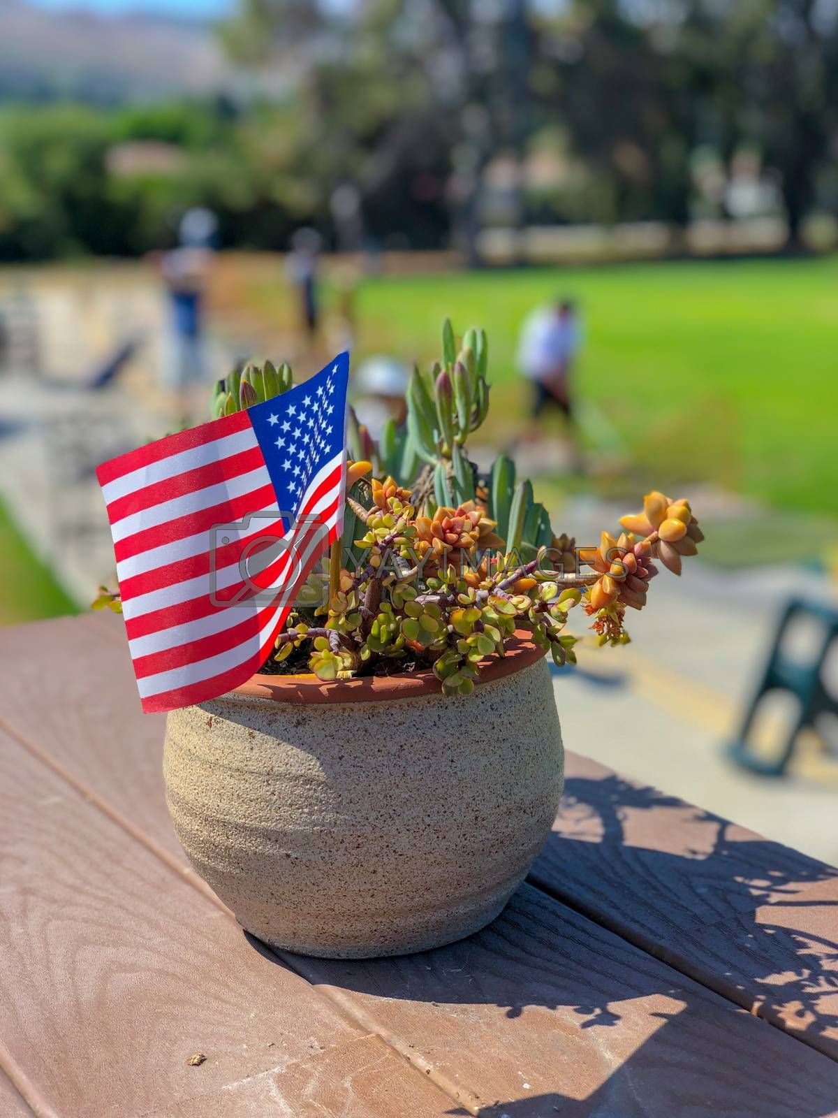 Patriotic flower pot with American flags and golfer on the background. American flag decoration.