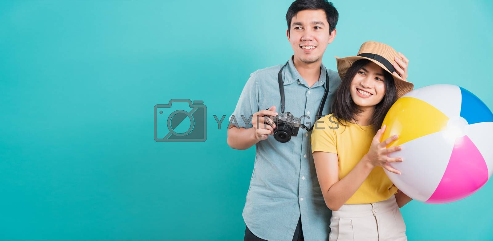 Happy Asian young beautiful woman handsome man couple in summer in holiday travel beach accessories ball and camera isolated on blue background with copy space for text