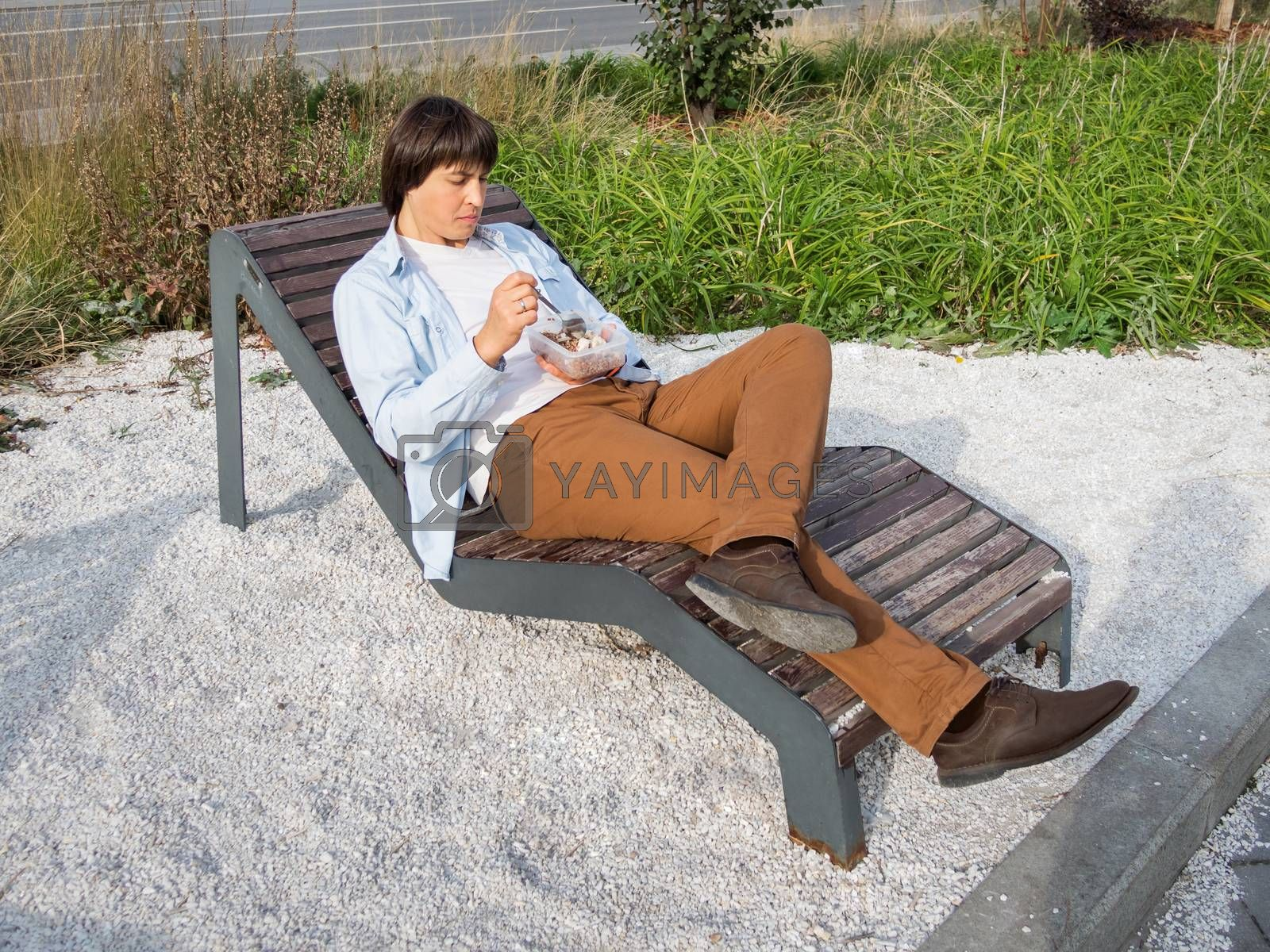 Man sits on park bench with take away lunch box. Healthy bowl with grains and meat. Casual clothes, urban lifestyle of millennials. Healthy nutrition.