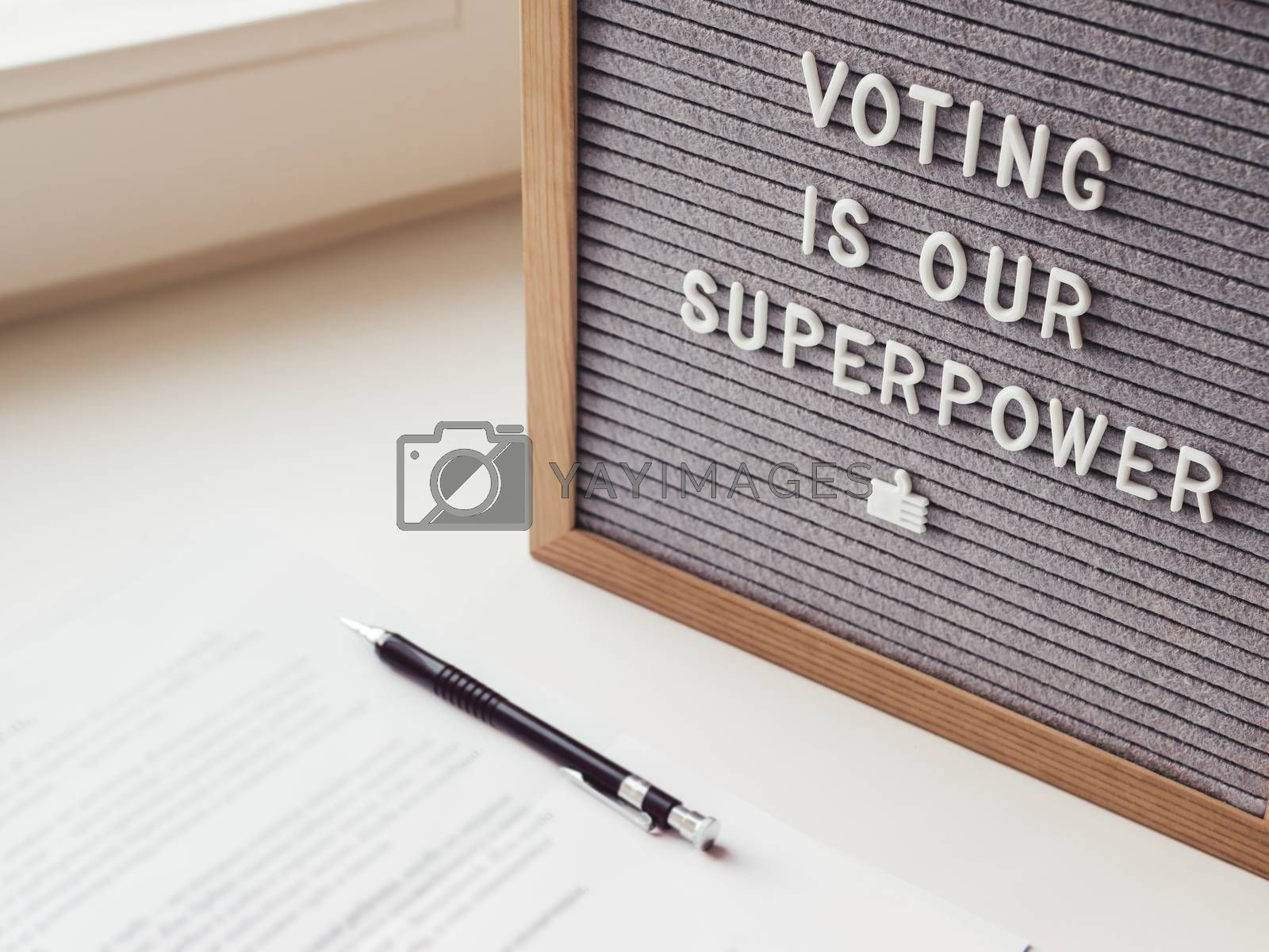 Letter board with phrase Voting is our superpower. Announcement of USA Presidential Election at 3rd November 2020. Call to go to the vote. Paper ballot and pen on window sill.