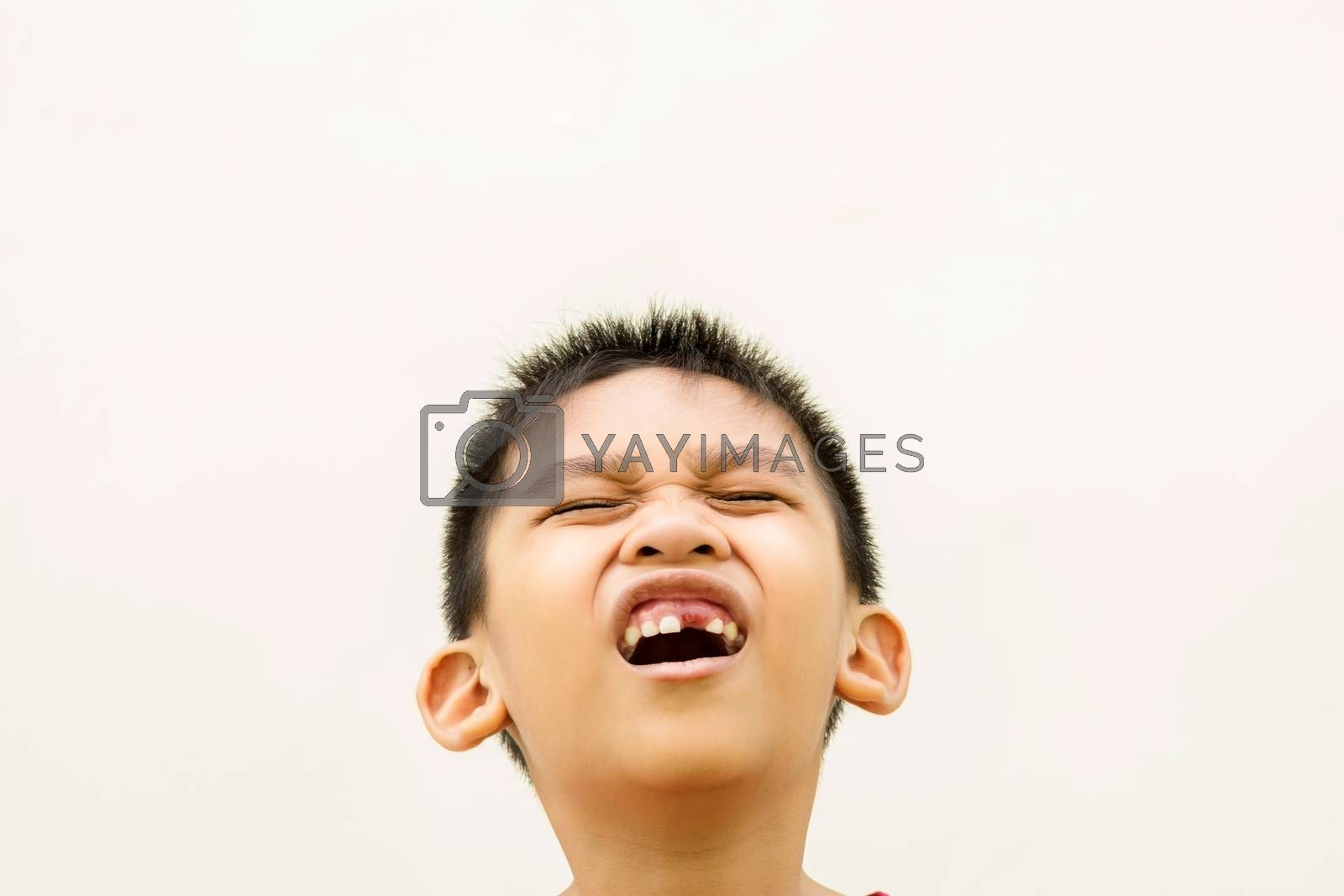 Close up in front of a boy singing in pain because of toothache.