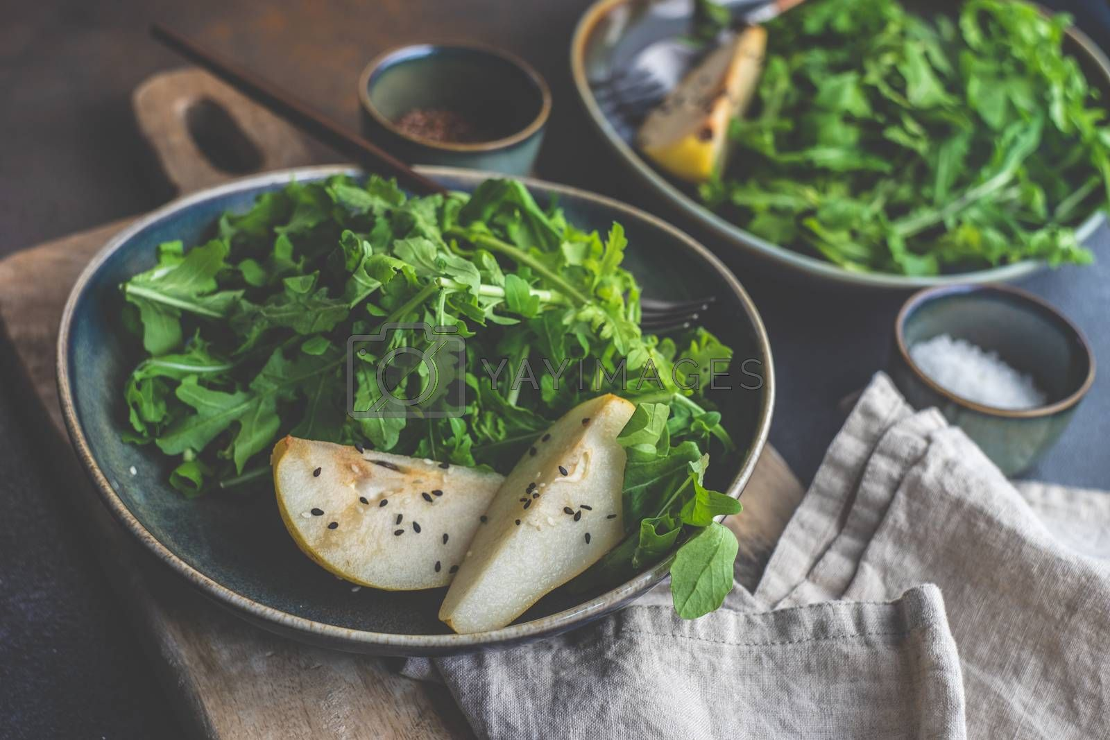 Organic food concept with fresh raw rucola leaves and pear slices with sesame seeds and olive oil on concrete background with copy space