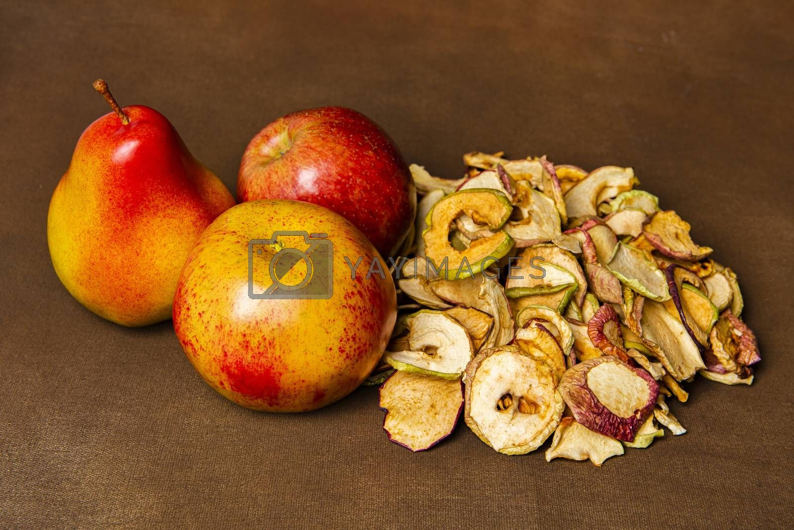 Pile of dried apples together with two whole apples and one pear. Still life concept of fall season harvest and homemade fruit processing
