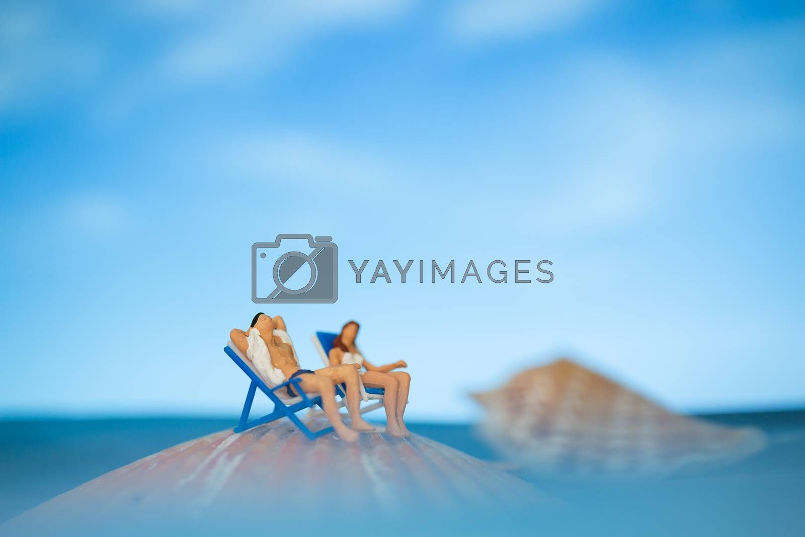 Miniature people sunbathing on a seashell with blue sky background  , summer vacation concept