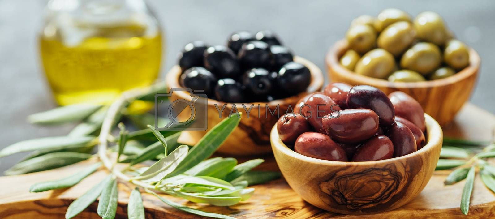 Set of green, red and black olives and olive oil on gray background. Different types of olives in olive wooden bowls and olive oil on wooden cutting board and olive leaves.Copy space.Horizontal banner