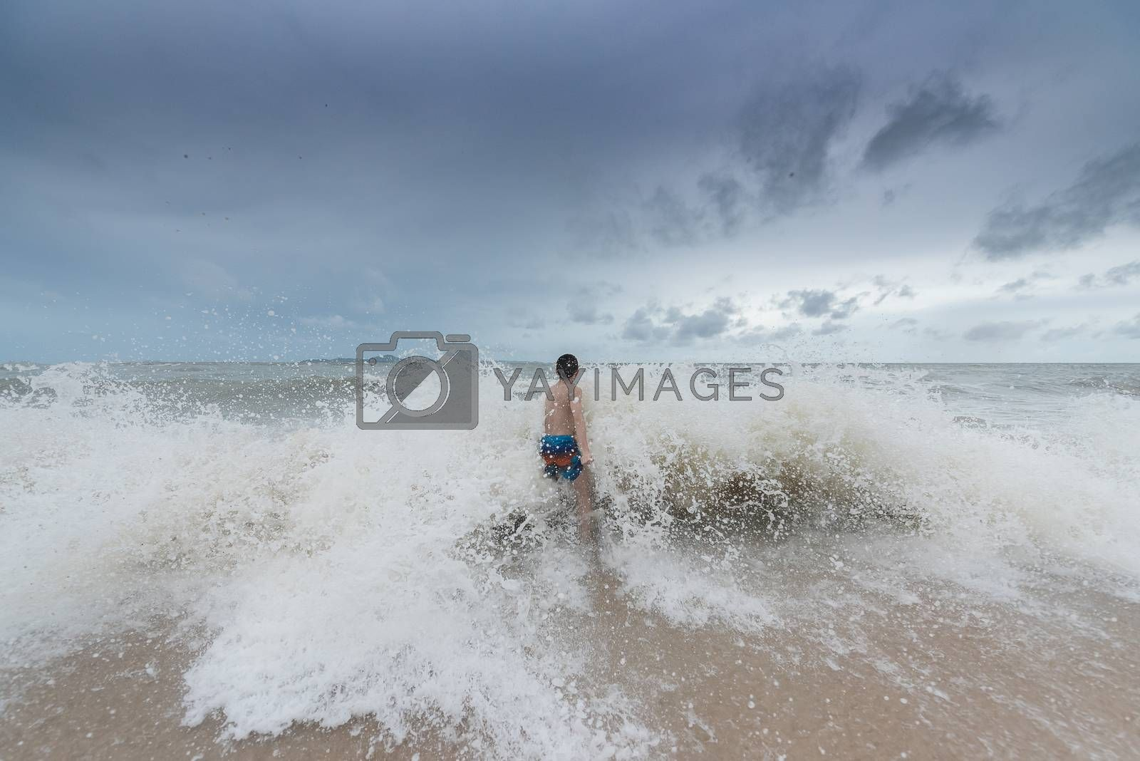 An Asian boy has felt happy and fun on the beach with a cloudy s by animagesdesign
