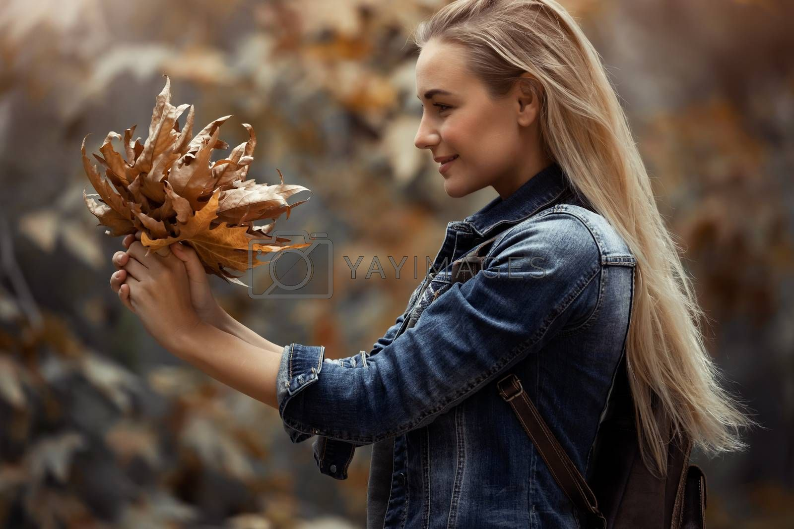 Profile Portrait of a Beautiful Blond Girl with Nice Bouquet of Dry Tree Leaves in the Park. Enjoying Beauty of Autumn Nature.