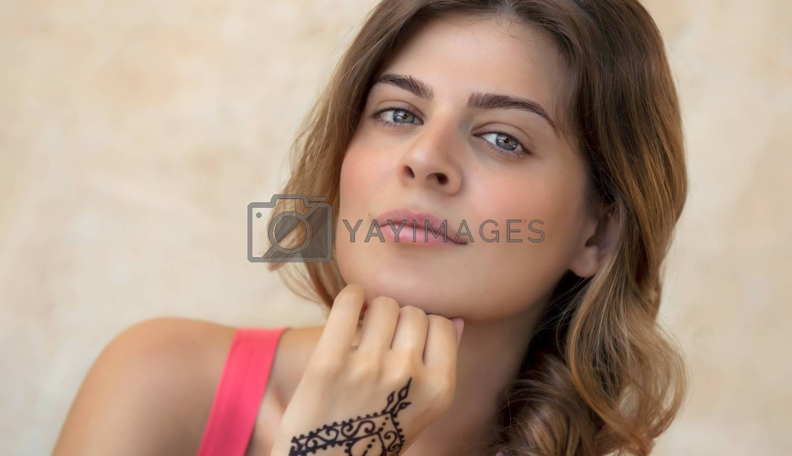 Genuine Portrait of an Attractive Woman Isolated on Beige Background with Beautiful Tattoo on the Hand. Stylish Body Art. Natural Beauty of Young Female.