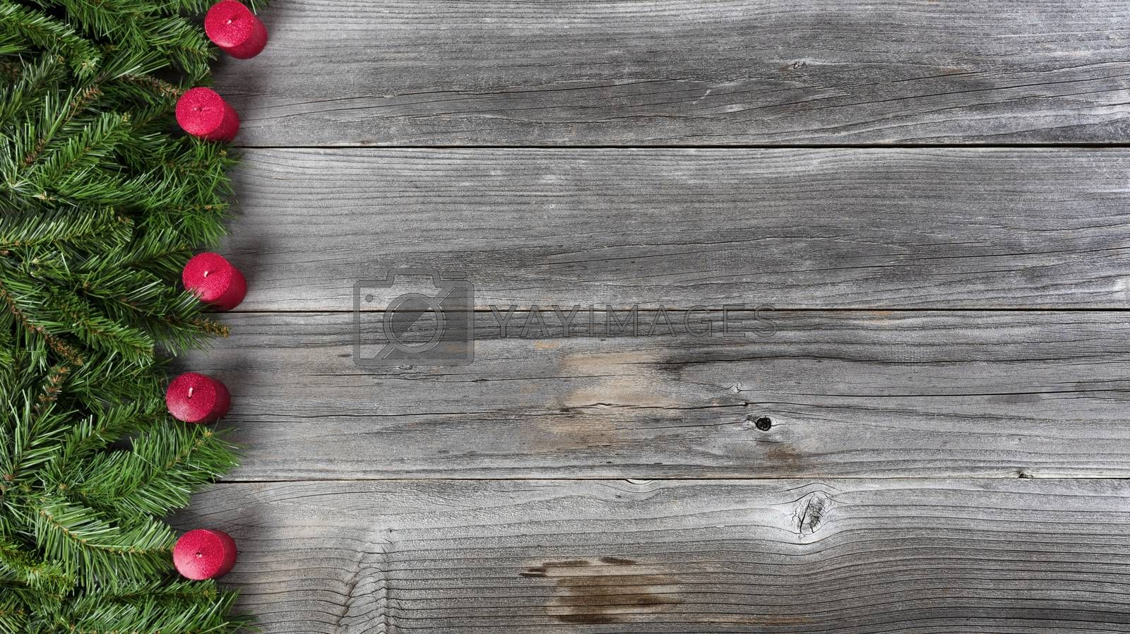 Merry Christmas and Happy New Year concept consisting of fir branches and red candles on left side of rustic wooden boards