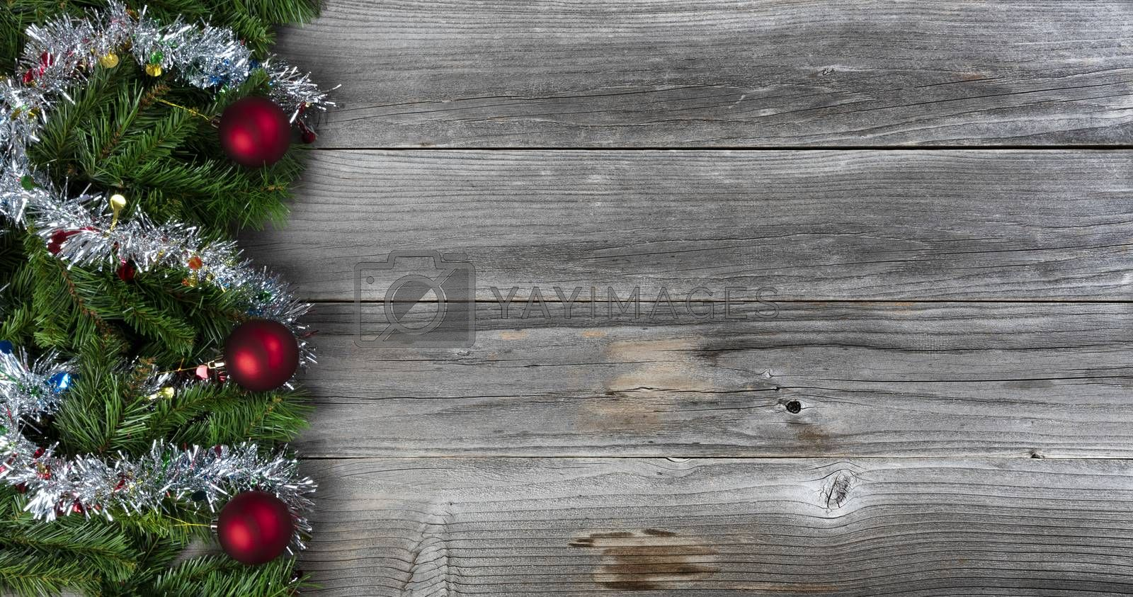 Merry Christmas and Happy New Year holiday concept with silver tinsel and red ball ornaments on rustic wood