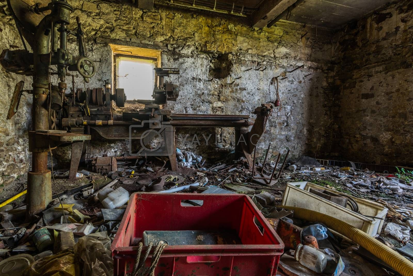 Old lathe in a workshop of an abandoned house