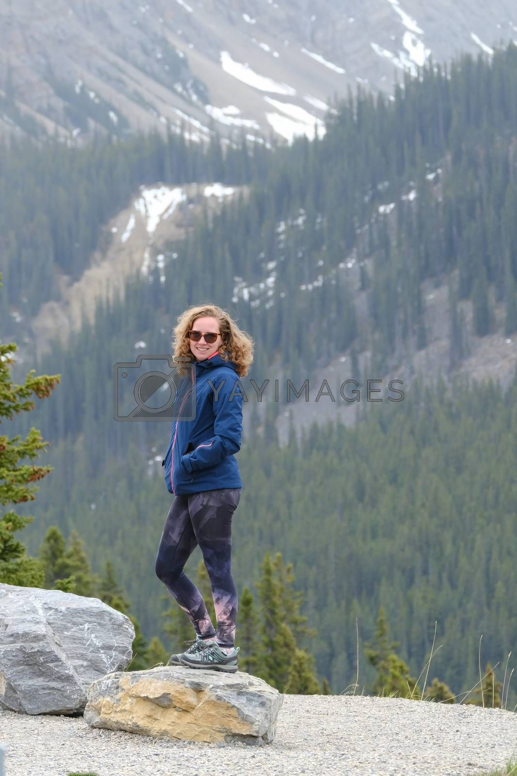 Woman standing on a big rock, casual clothing. Lake Louise in Rocky Mountains. Banff National Park. Alberta. Canada.