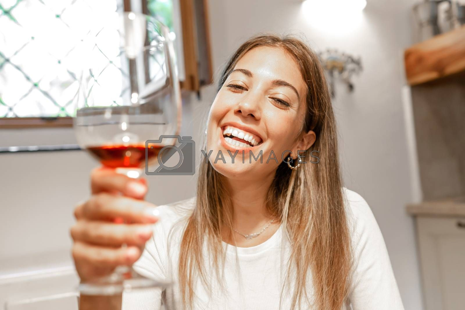 Cute young caucasian blonde woman toasting with red wine glass looking at the camera at home - New normal remote conference communication by online technology for the Coronavirus pandemic