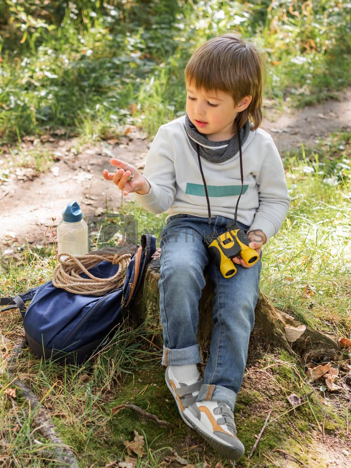 Little explorer on hike in forest. Boy with binoculars and compass sits on stump and reads map. Outdoor leisure activity for children. Summer journey for young tourist.