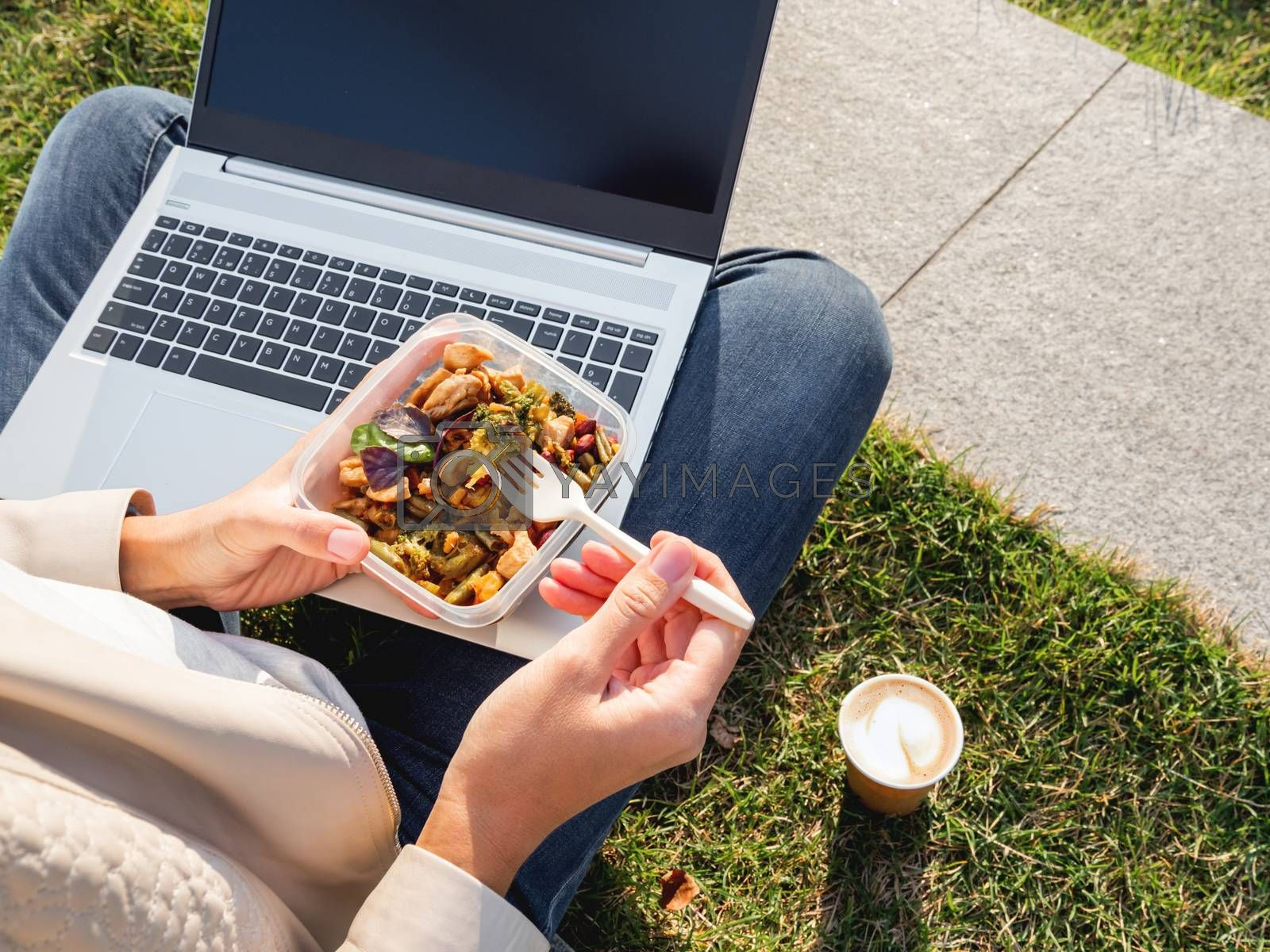 Woman sits on park bench with laptop and take away lunch box, cardboard cup of coffee. Healthy bowl with vegetables. Casual clothes, urban lifestyle of millennials. Healthy nutrition.