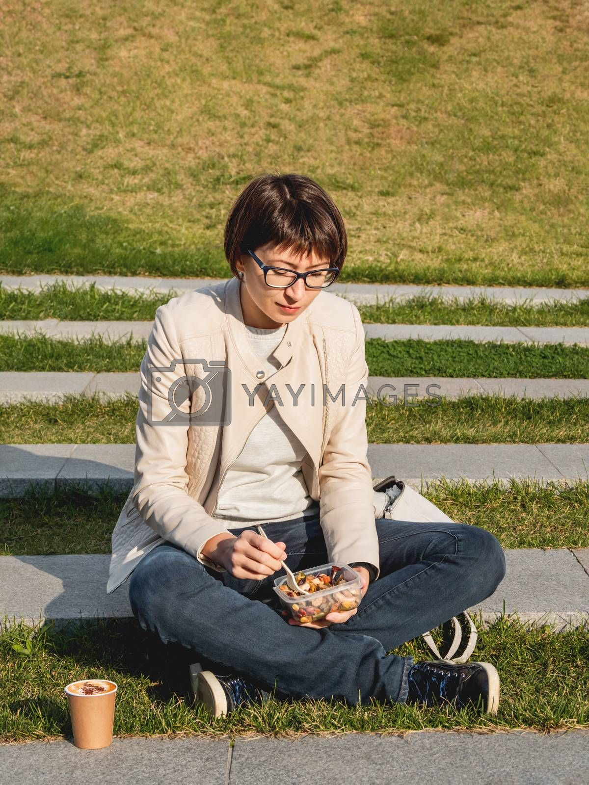 Woman sits on park bench with take away lunch box, cardboard cup of coffee. Healthy bowl with vegetables. Casual clothes, urban lifestyle of millennials. Healthy nutrition.