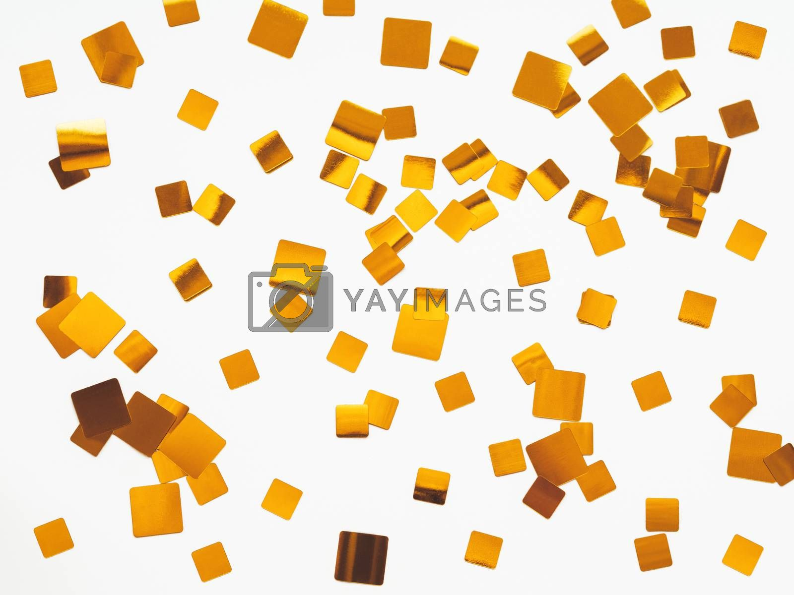 Festive background with golden square confetti on white background. Holiday backdrop for Christmas and New Year cards. Flat lay, top view.