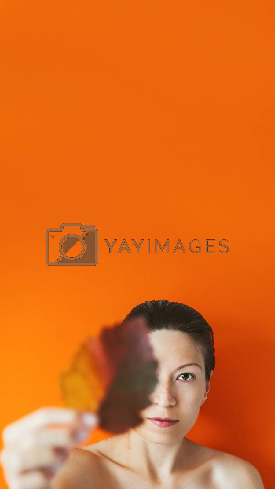 Portrait of Asian woman closing her eye with autumn leaf. Model on orange monochrome background. Natural beauty on bright and colorful backdrop. Banner with copy space.