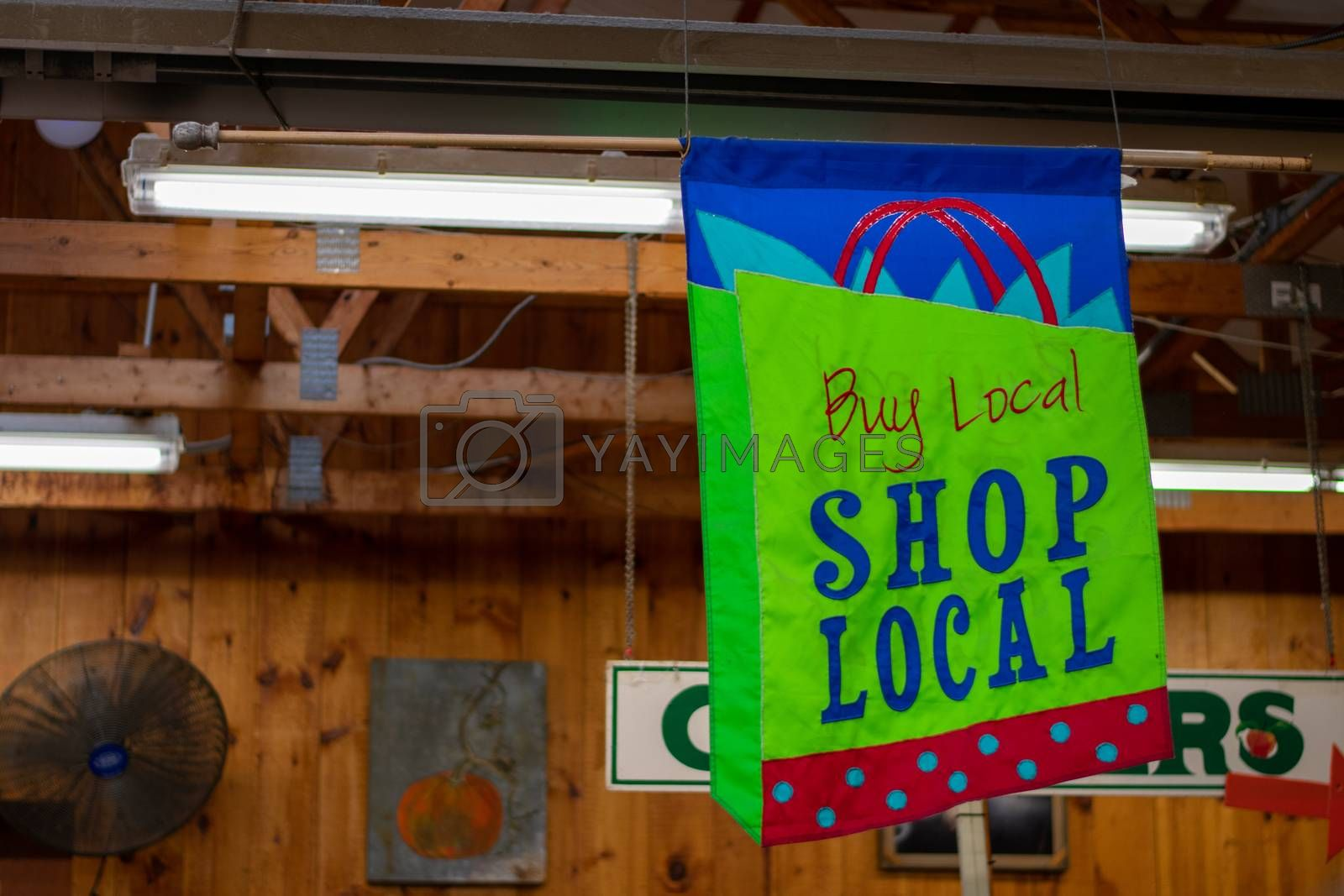 A Hanging Sign in a Wooden Farmer's Market That Says Buy Local Shop Local