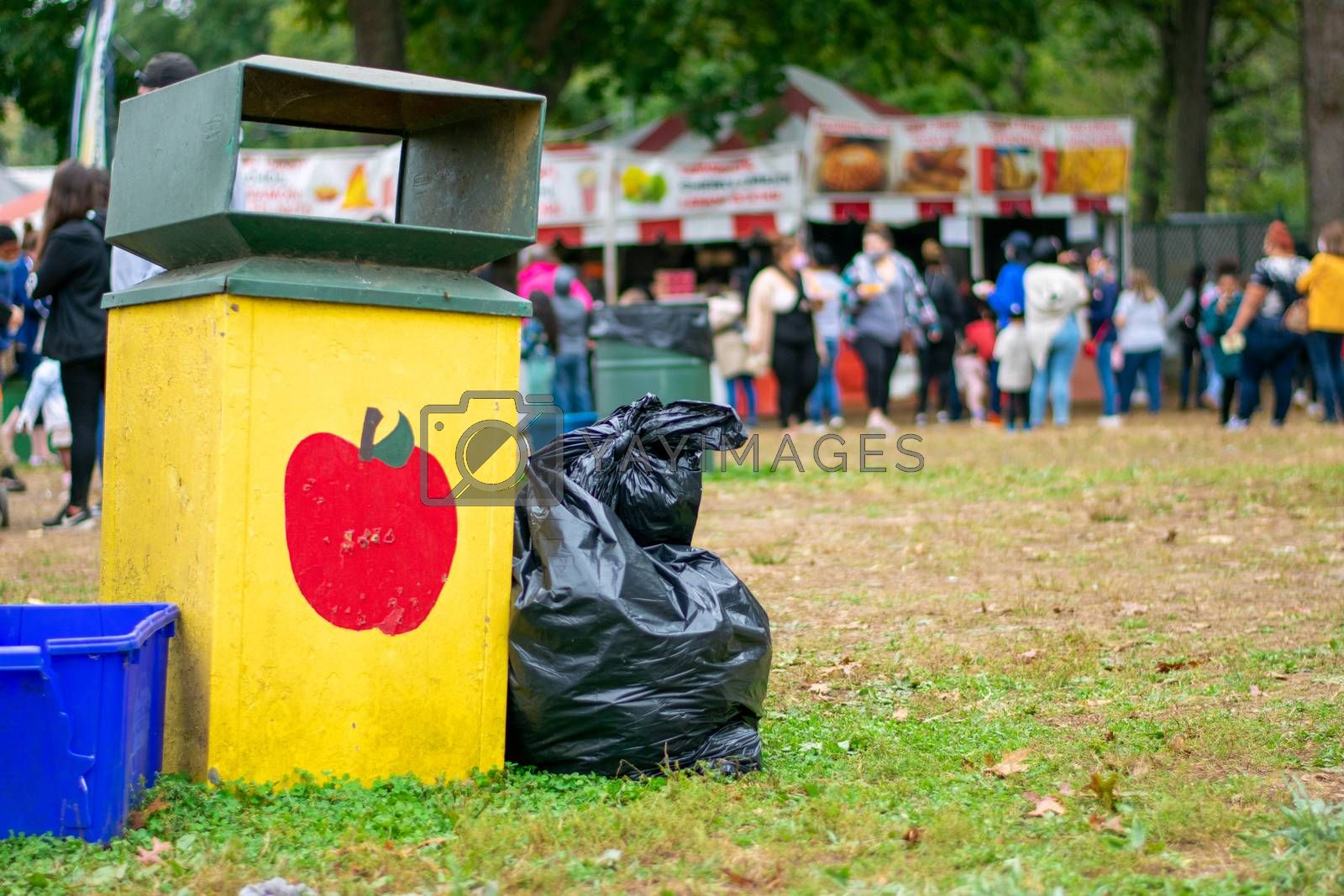 A Yellow Trash Can at a Carnival With an Apple Painted on It
