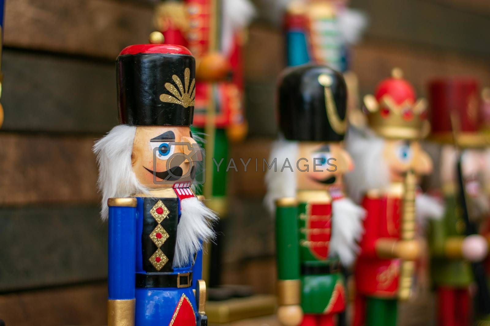 A Blue Nutcracker on a Dark Wooden Shelf With Other Nutcrackers In Line Next to It