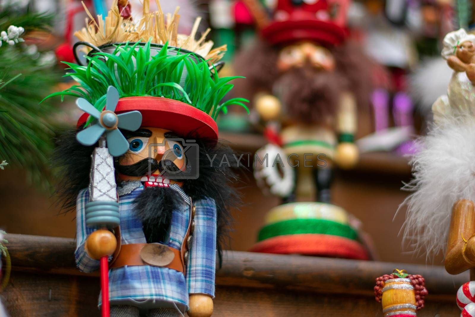 A Funny Looking Nutcracker on a Wooden Shelf In Line With Other Nutcrackers