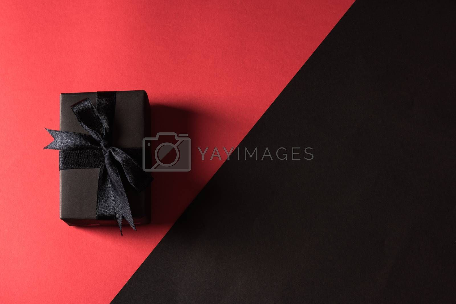 gift box wrapped in black paper and black bow ribbon by Sorapop