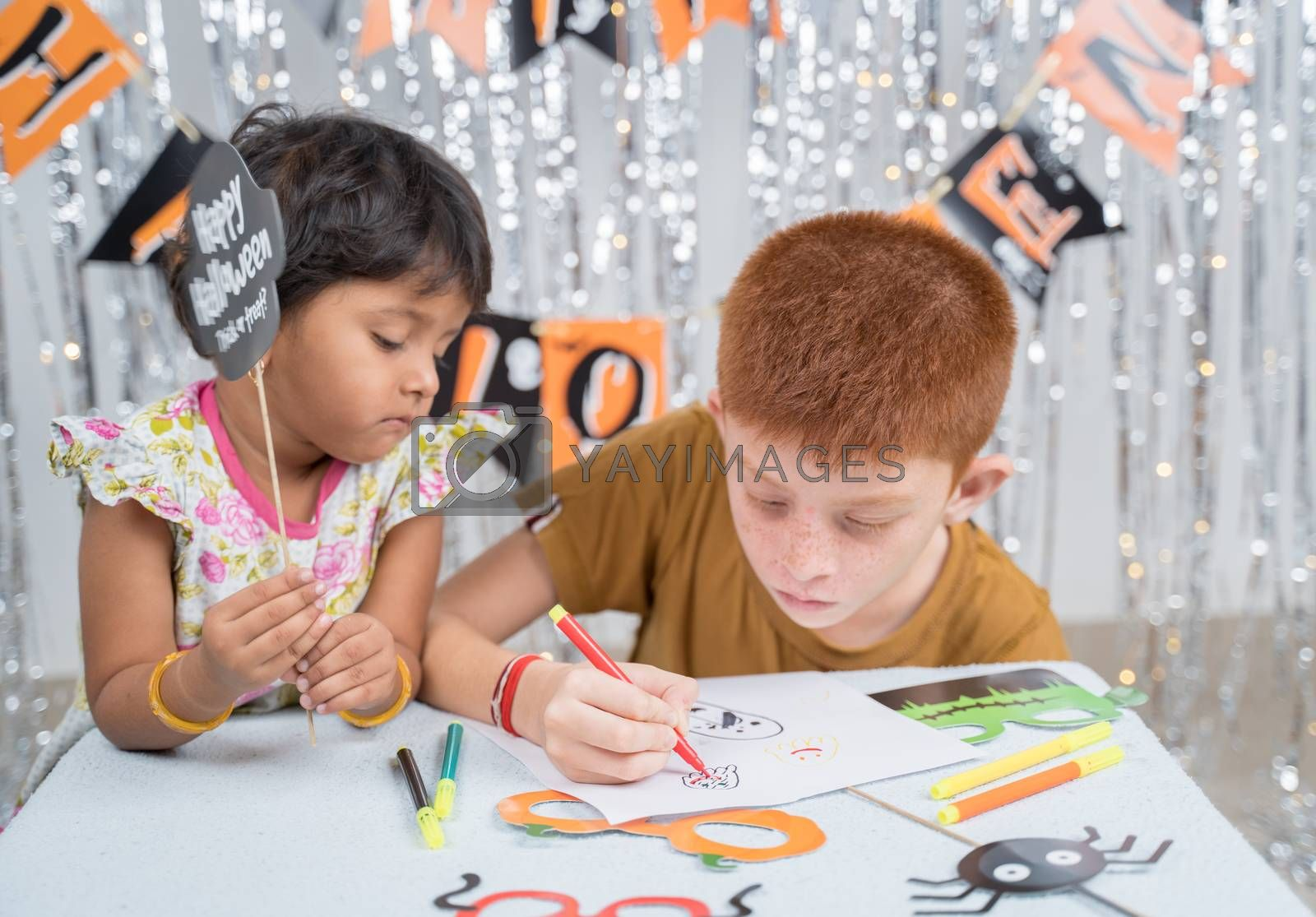 Selective focus on drawing hands, Kids busy in making or drawing halloween props - concept of halloween, holiday and childhood festival celebration and preparation