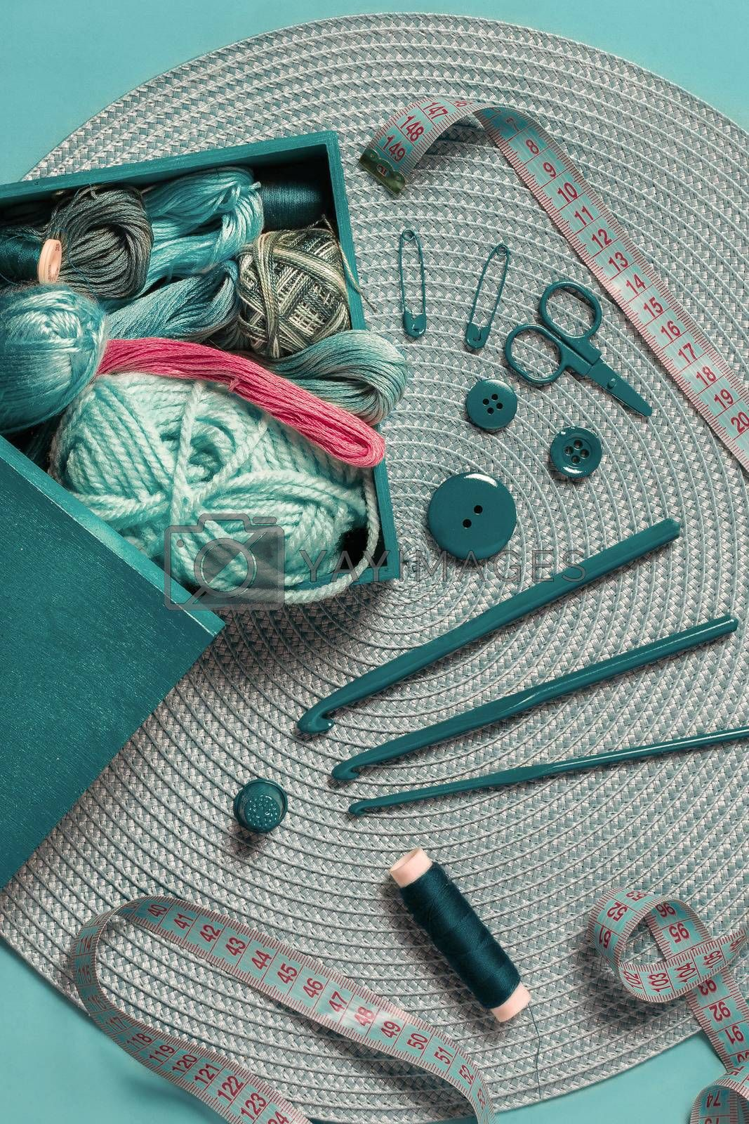 crochet needles for knitting balls of wool threads and tape measure on a green textured table in overhead view