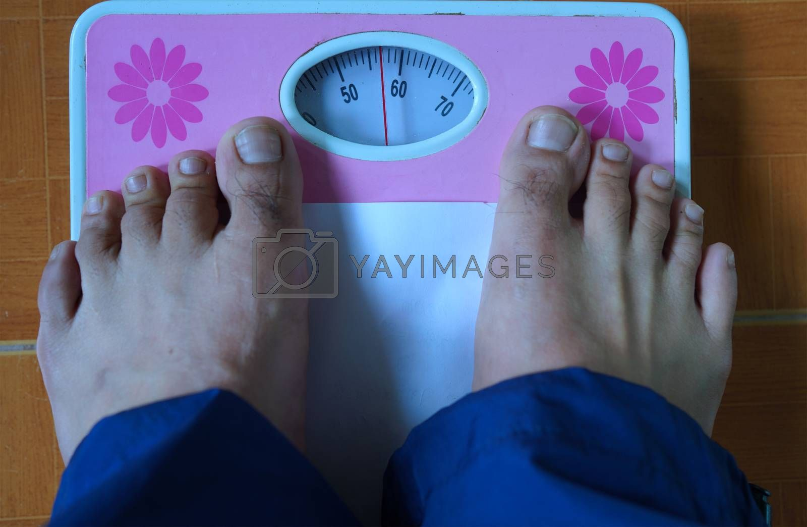 Foot on the weight scale, health and weight management concept.