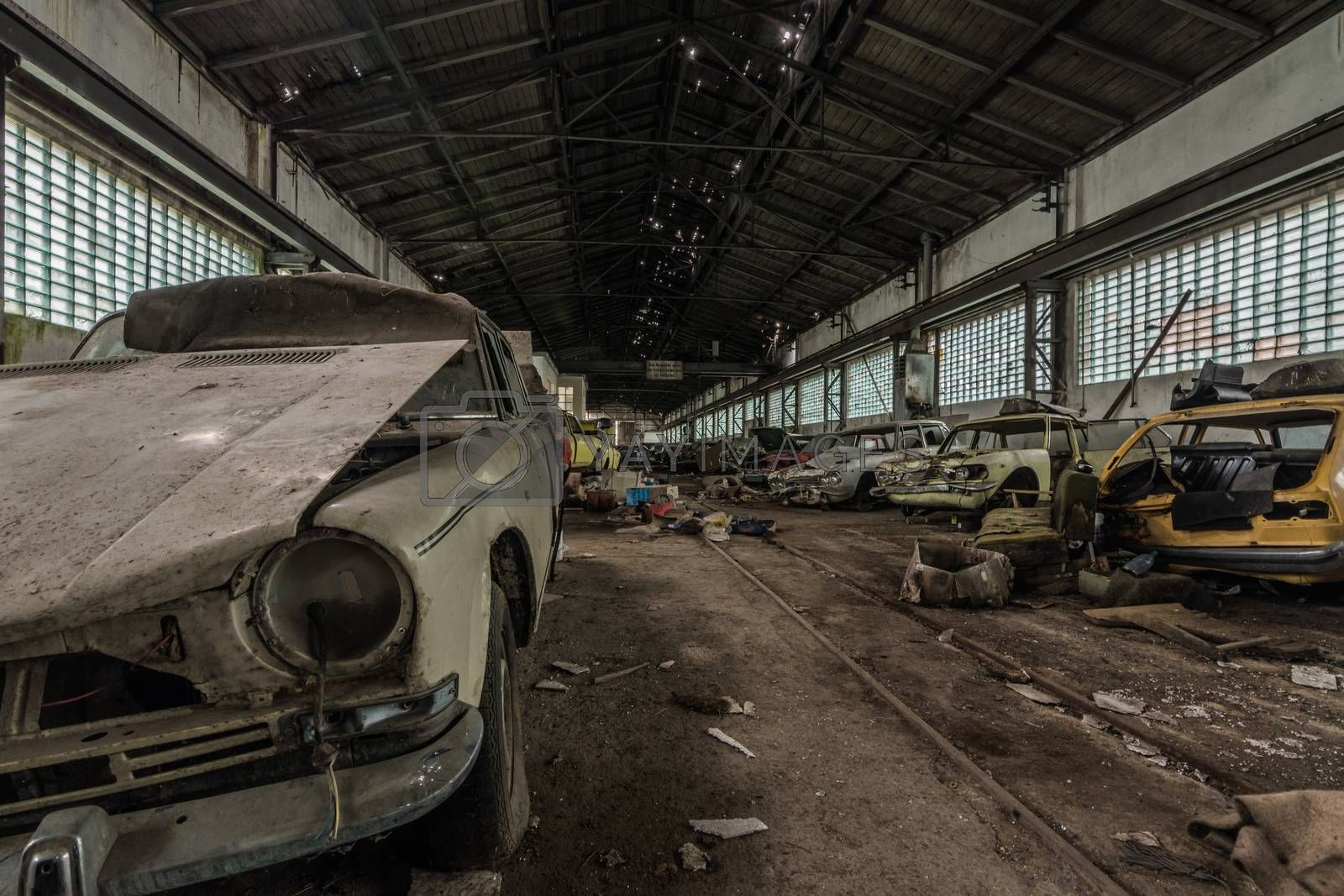 many disassembled cars in a hall of a garage