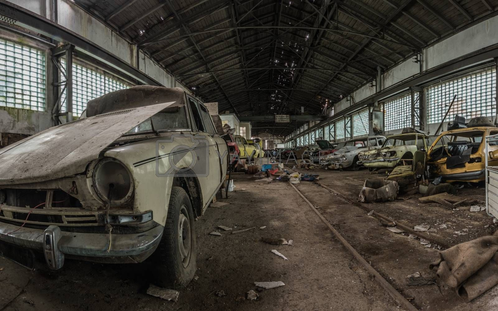 many disassembled cars in a hall panorama view