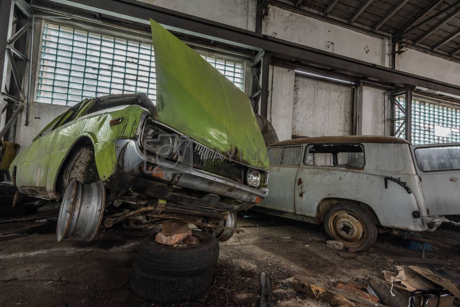 old green obliquely car in a hall of a garage