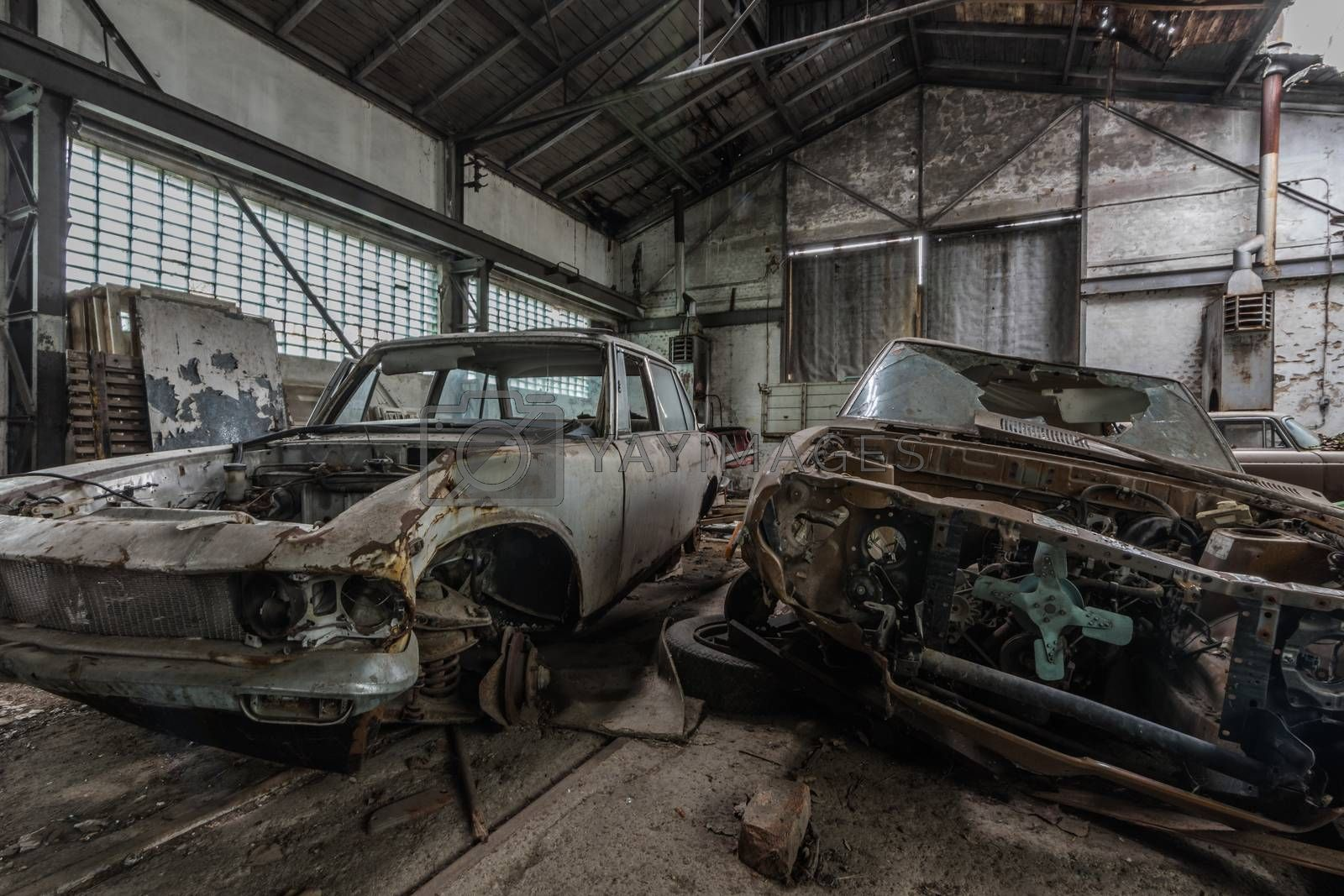 two disassembled rusty cars in a garage