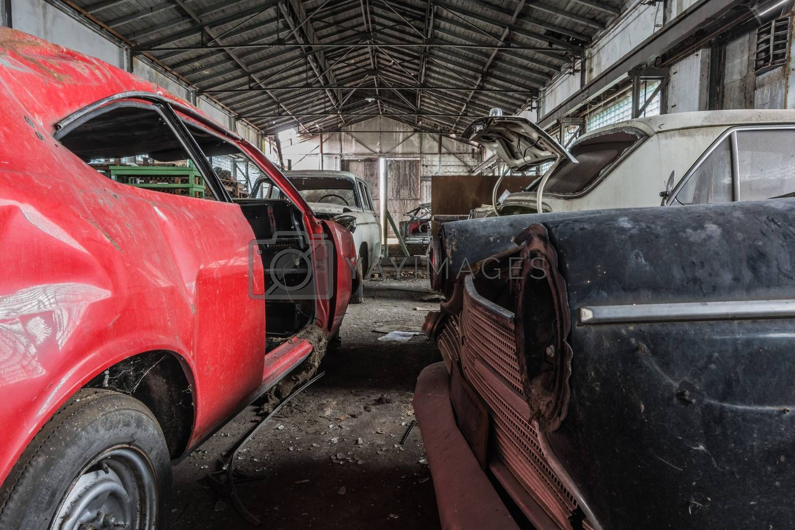 disassembled old cars in a large abandoned hall
