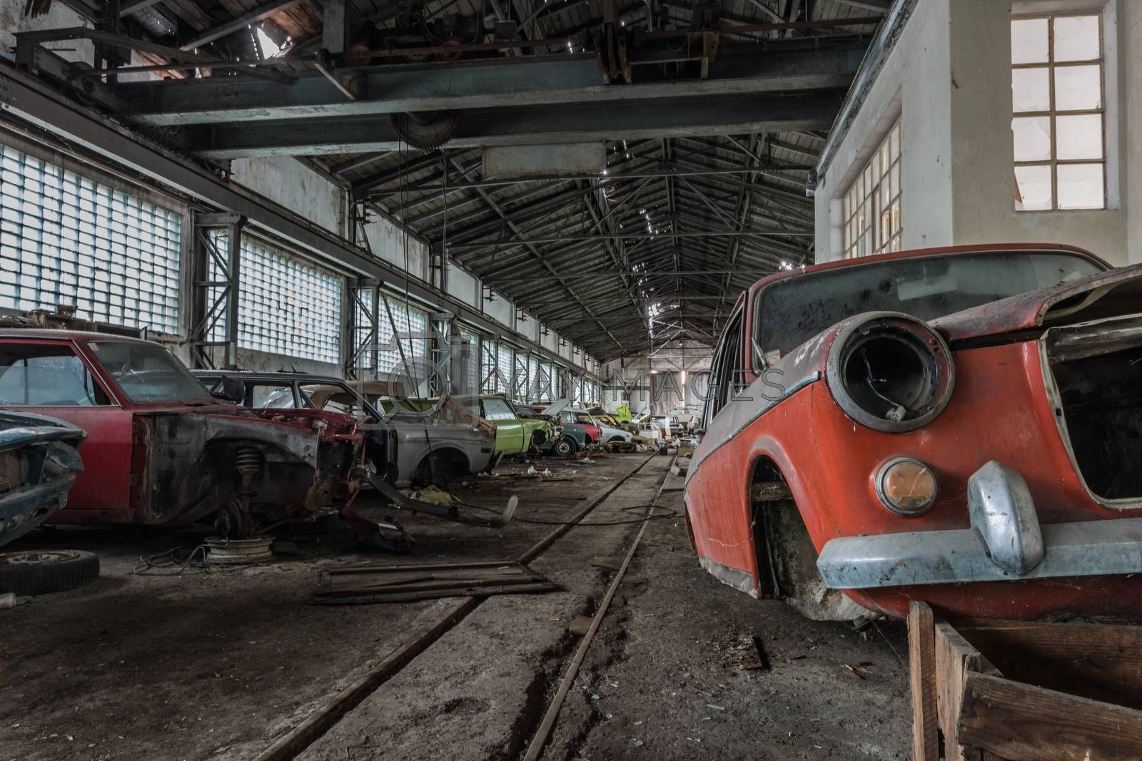 lots of colorful cars in an abandoned big hall