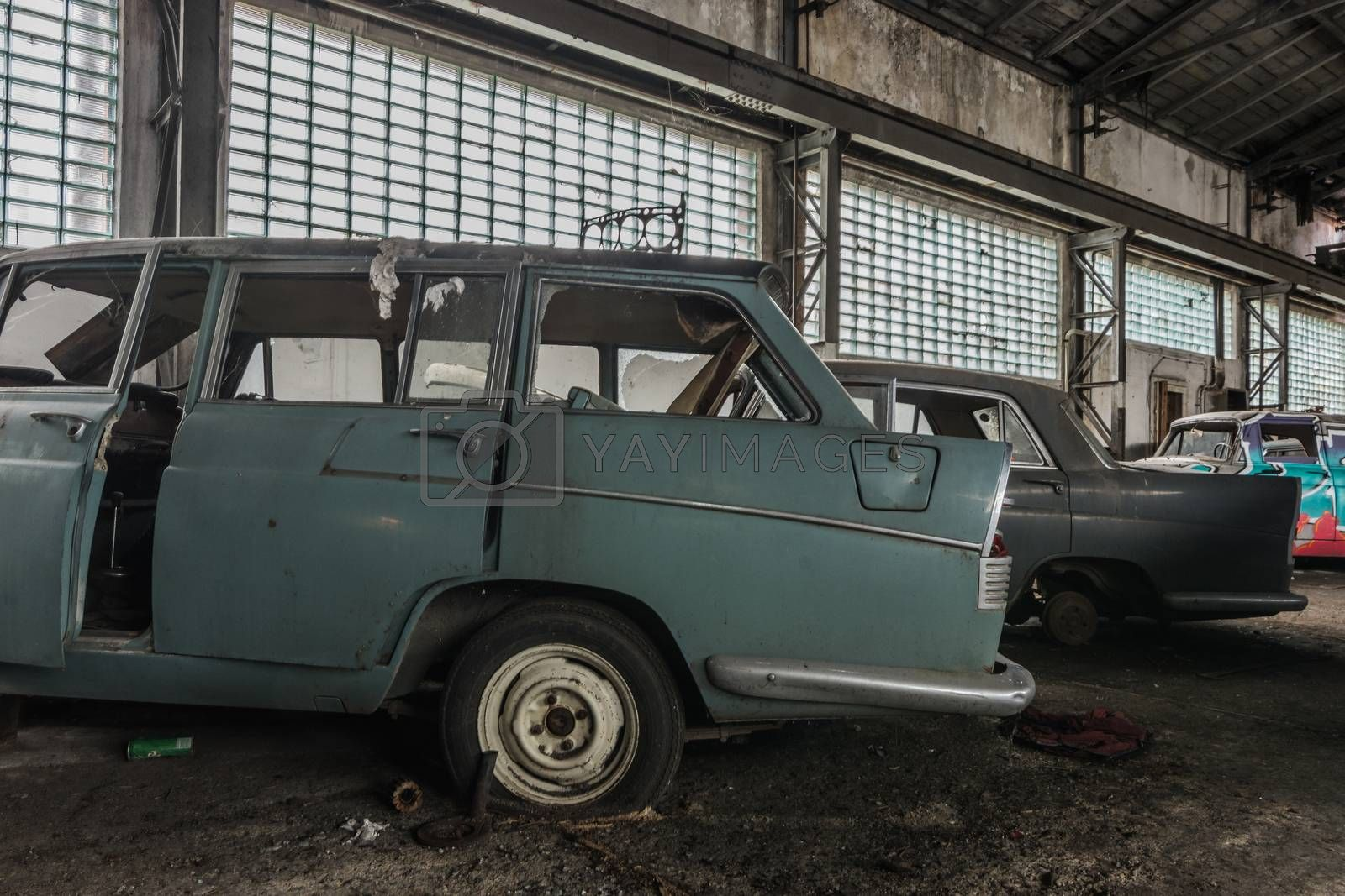 Old cars in a hall with windows from an auto repair shop