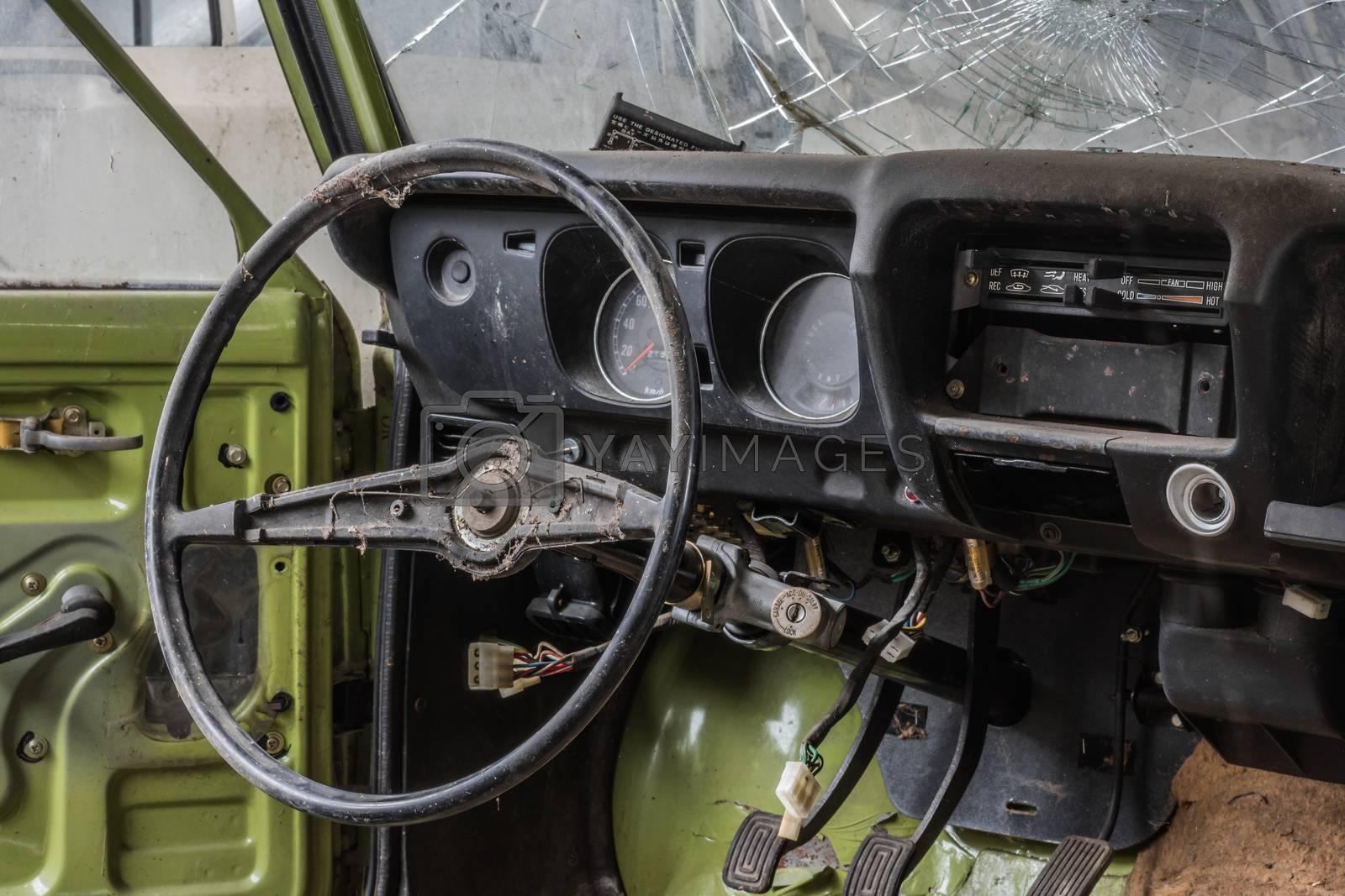 Steering wheel of old green car in an car repair shop