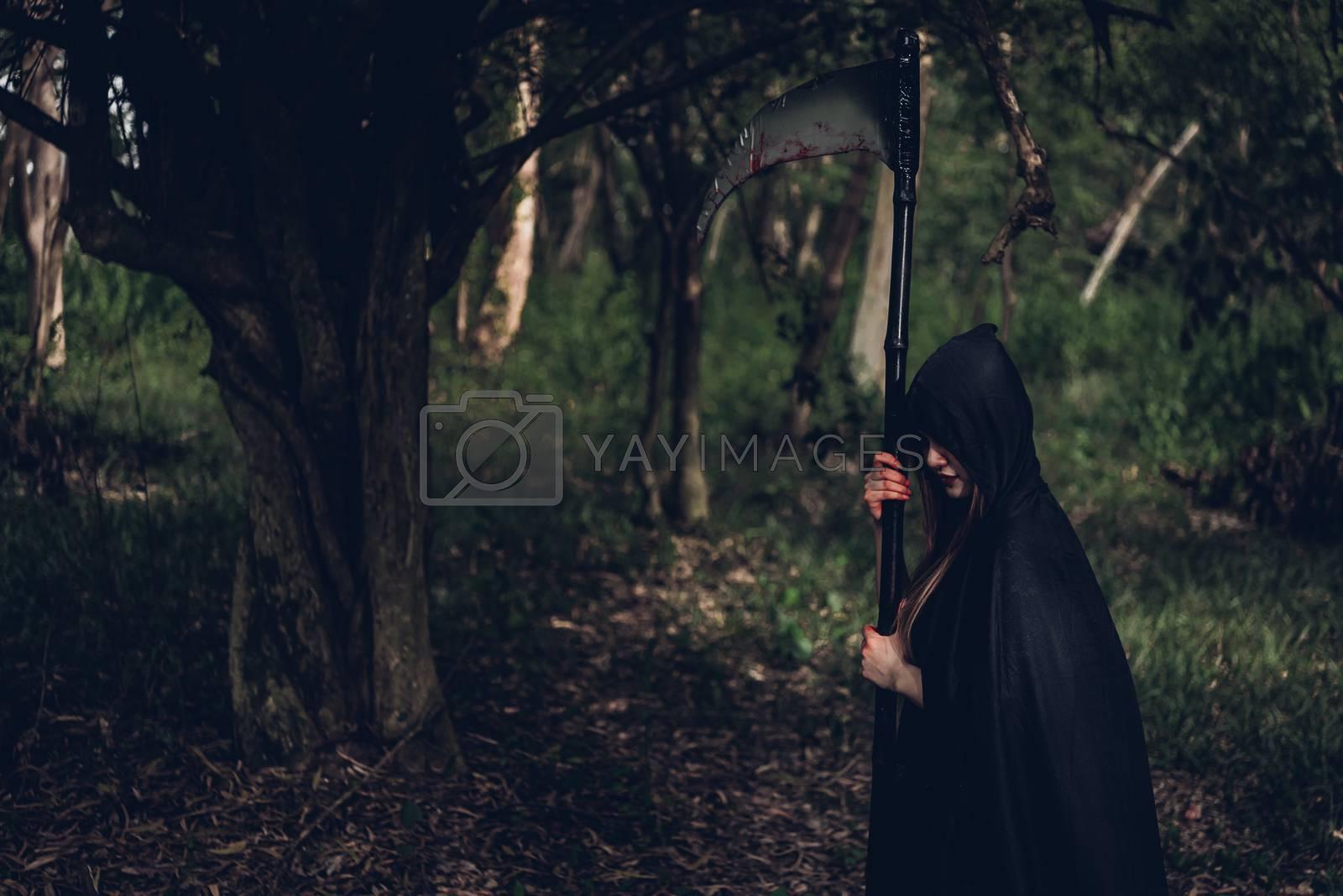 Woman horror ghost holding reaper in forest by Sorapop