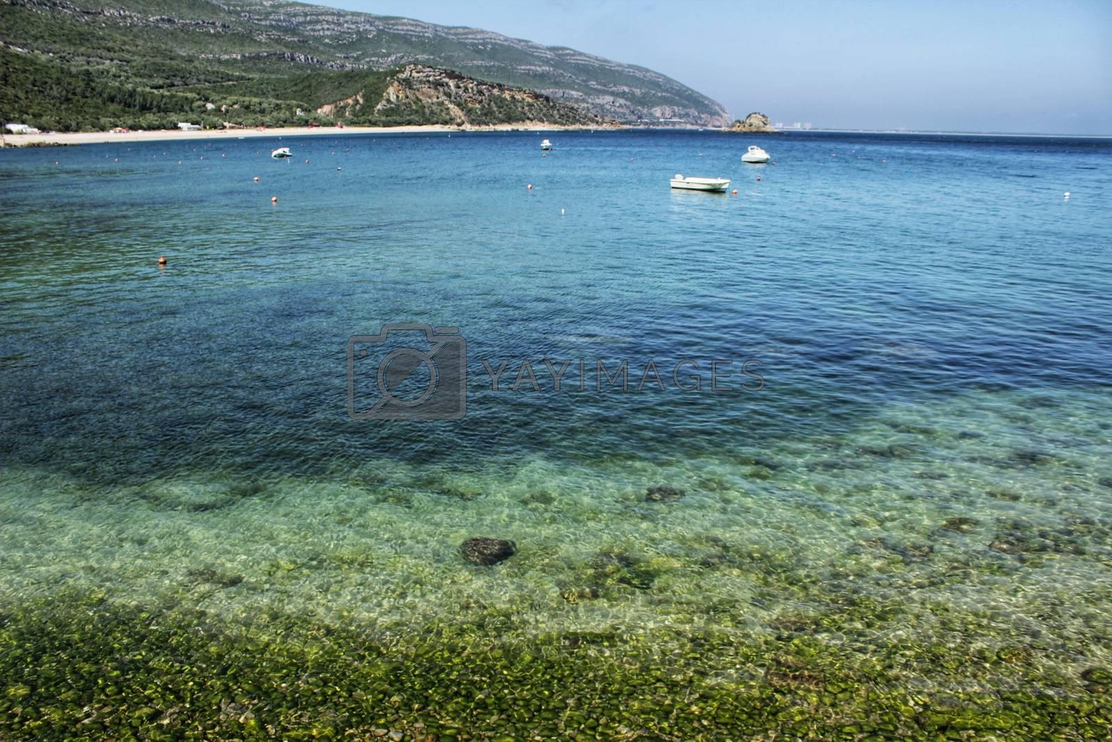 Crystalline waters of Portinho Beach between mountains in Portugal