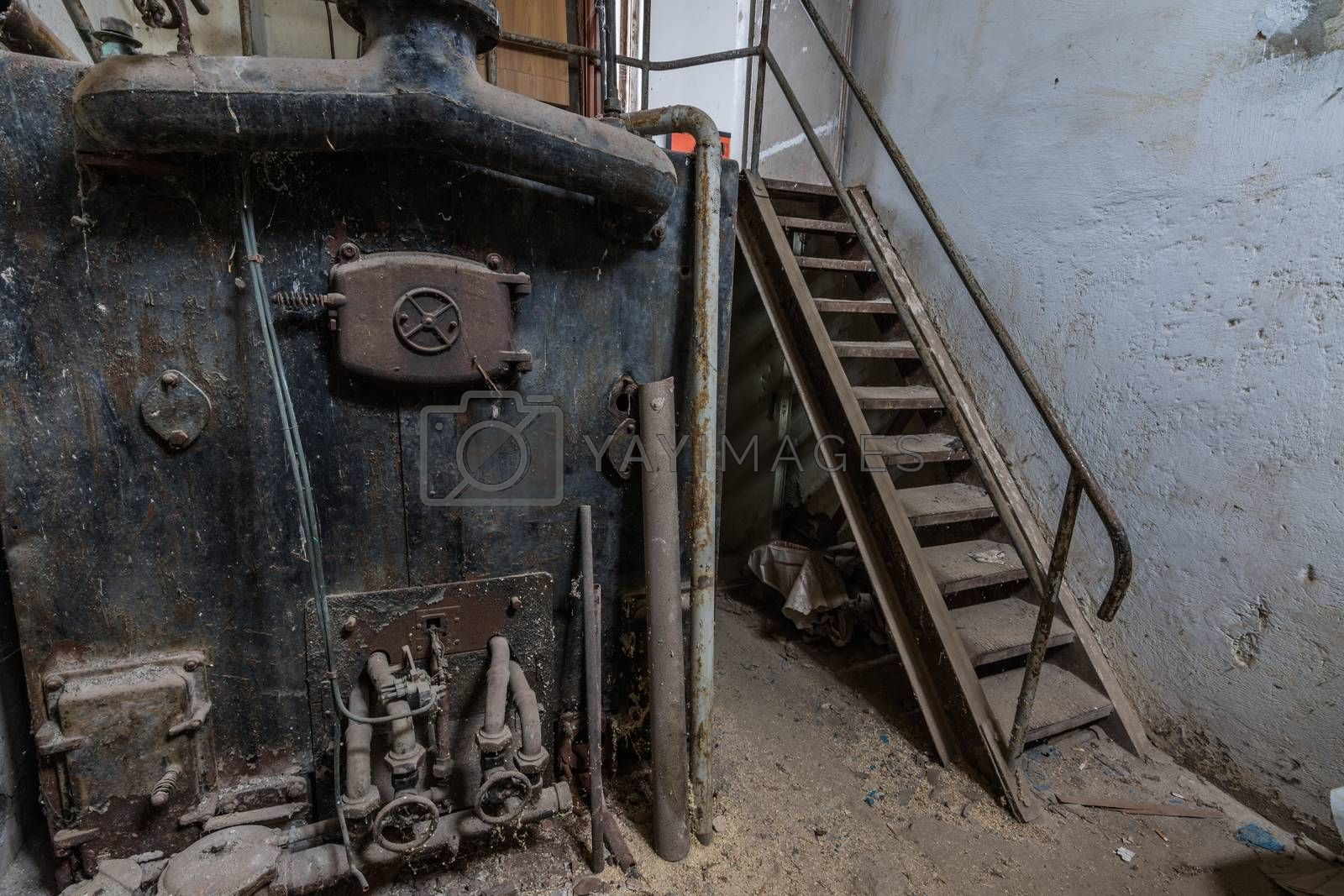 Rusty oven and stairs in a cellar of a house