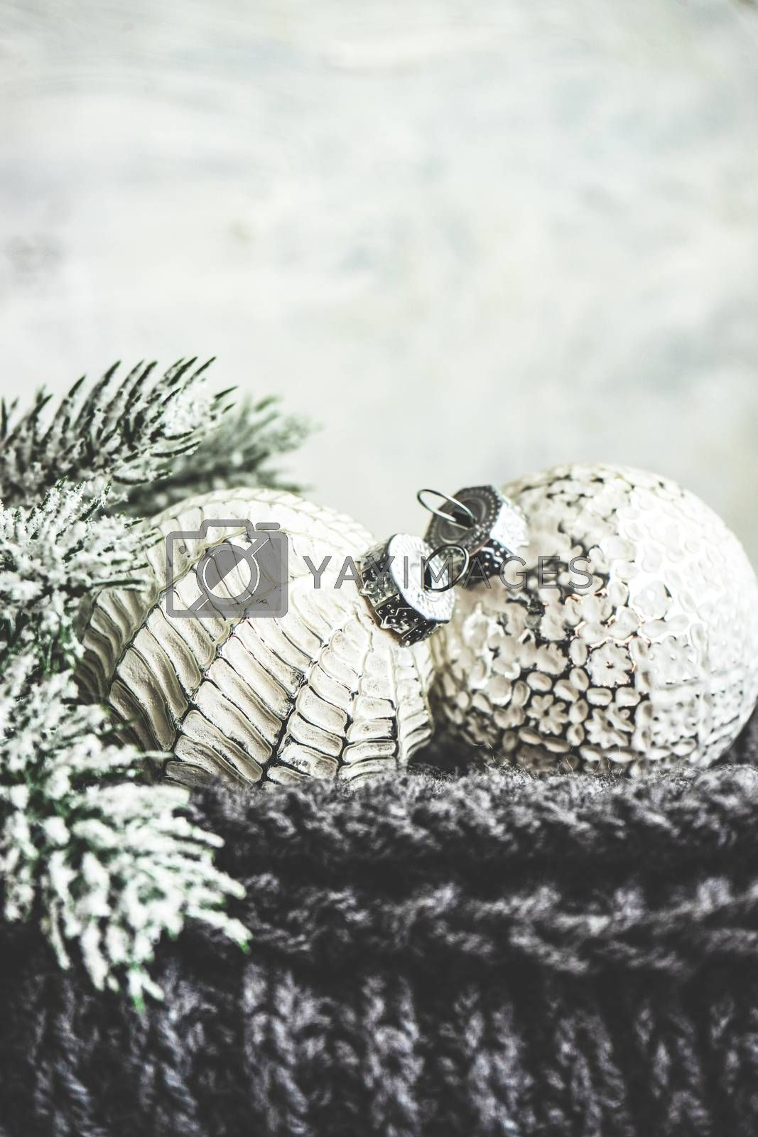 Monochrome Christmas card concept with knitted scarf and vintage baubles on wooden background with copy space